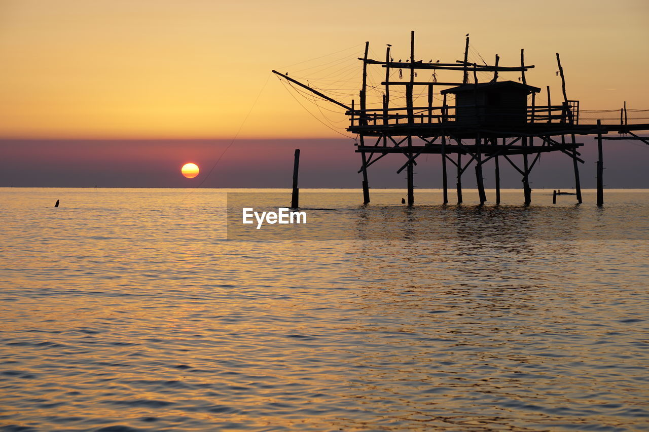 sunset, water, sky, sea, architecture, horizon over water, built structure, waterfront, orange color, horizon, tranquil scene, scenics - nature, beauty in nature, nature, tranquility, silhouette, no people, sun, pier, outdoors, fishing industry