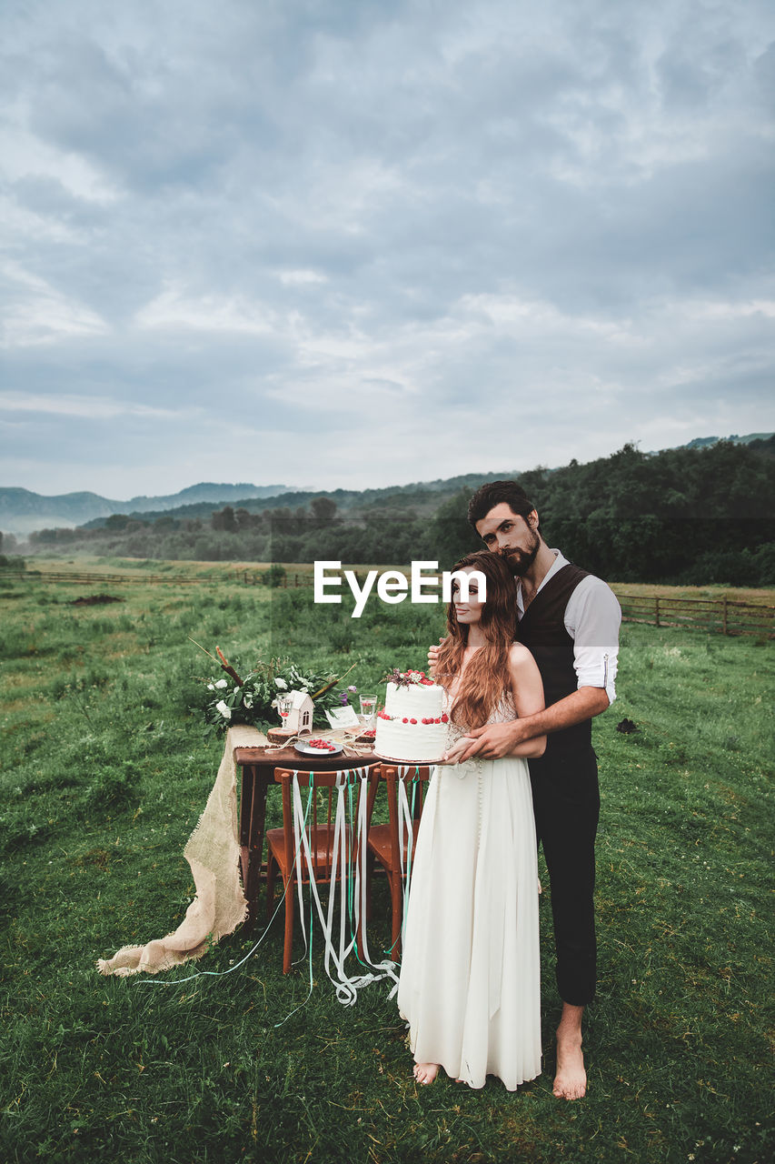 Full length of young couple holding wedding cake while standing on field against cloudy sky