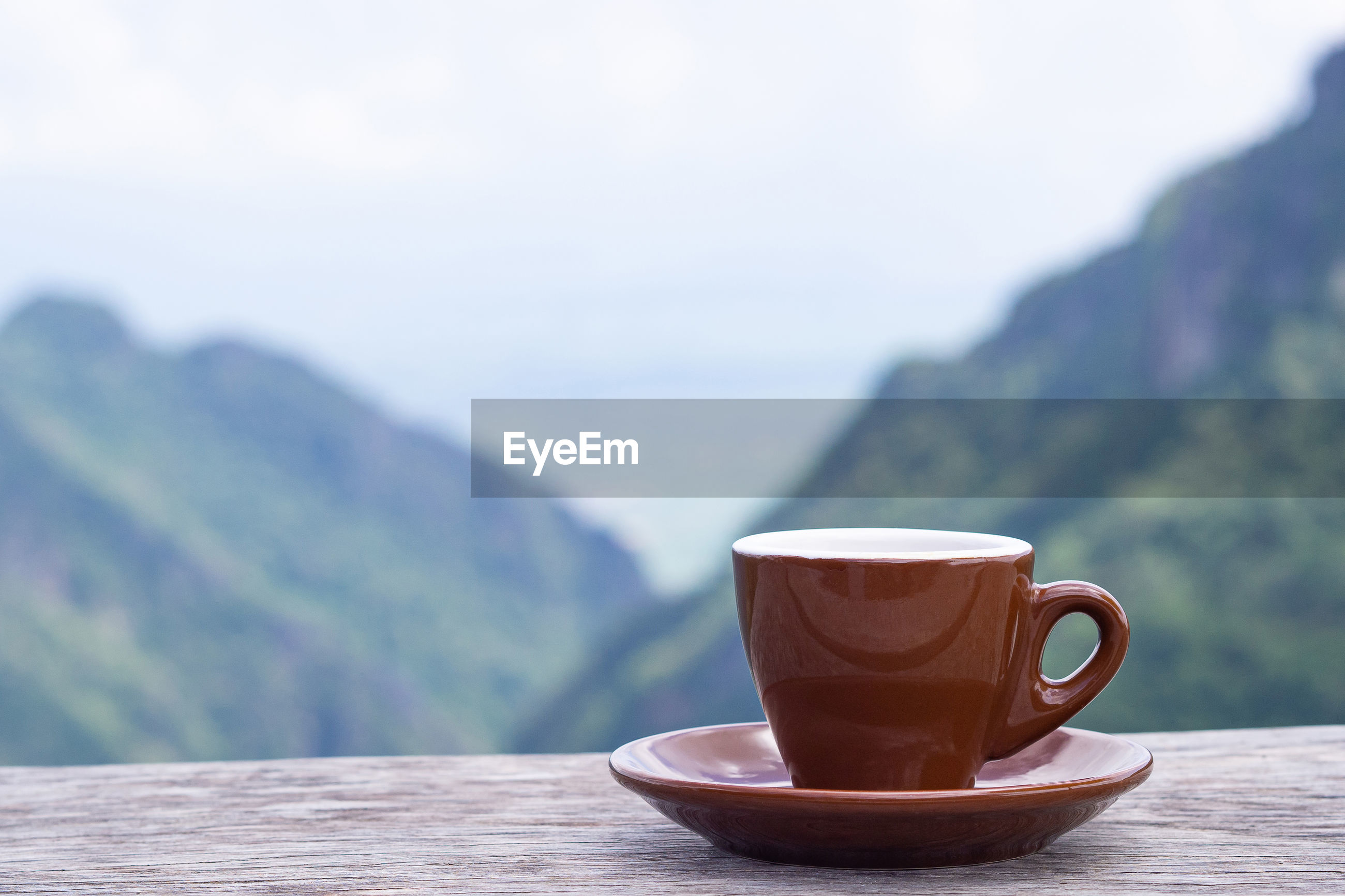 A brown coffee cup on wooden table with beautiful scenery view of mountains.