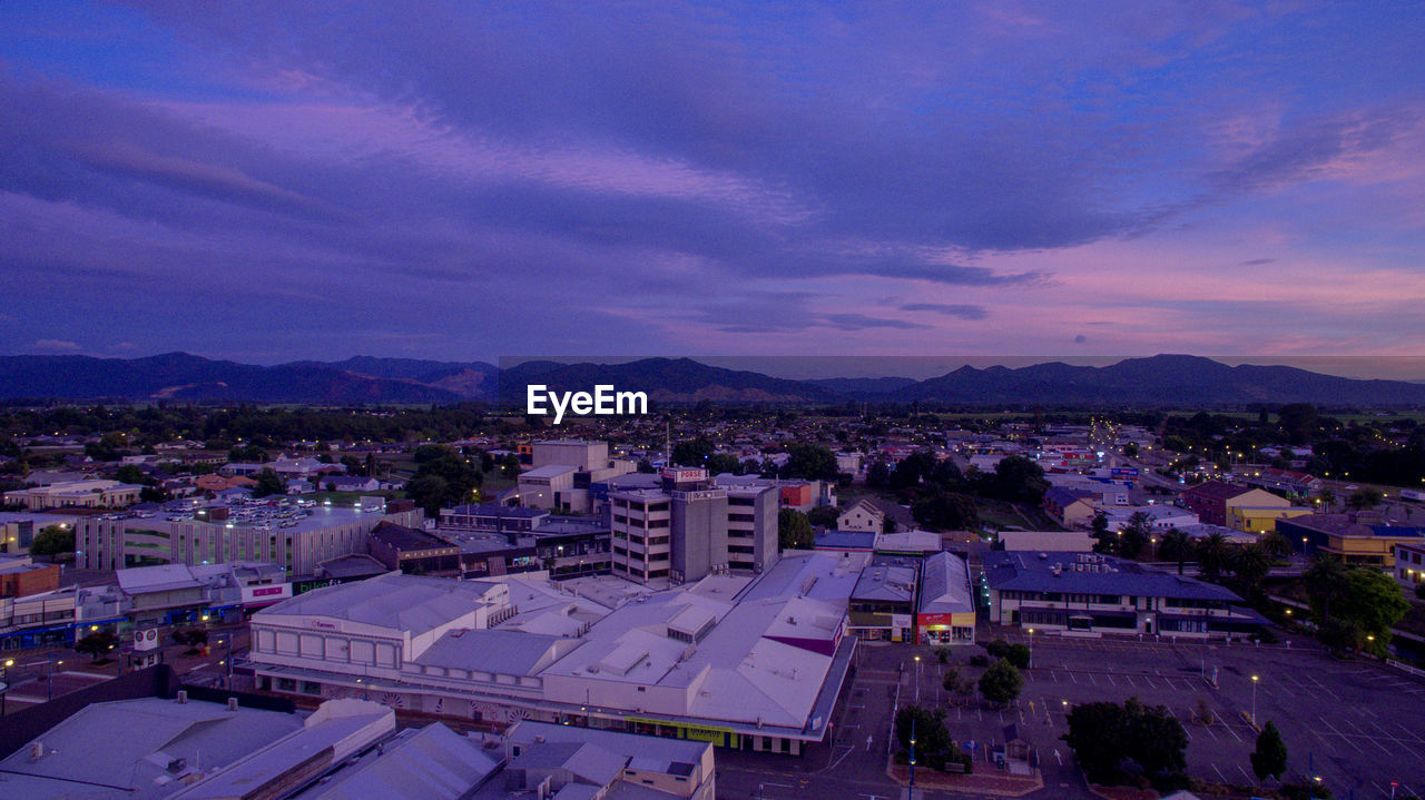sky, architecture, building exterior, built structure, city, cloud - sky, mountain, high angle view, nature, no people, building, residential district, cityscape, outdoors, sunset, dusk, mountain range, environment, beauty in nature, scenics - nature, townscape