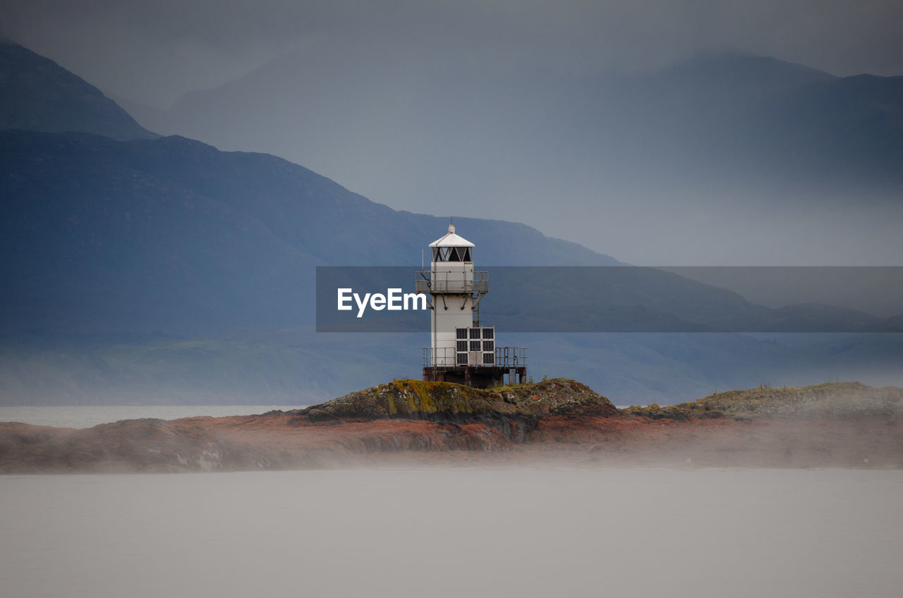 LIGHTHOUSE ON BUILDING BY MOUNTAINS AGAINST SKY