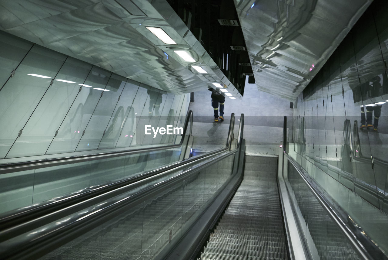 transportation, architecture, indoors, modern, direction, railing, moving walkway, the way forward, escalator, built structure, empty, convenience, illuminated, staircase, incidental people, public transportation, ceiling, absence, diminishing perspective, motion