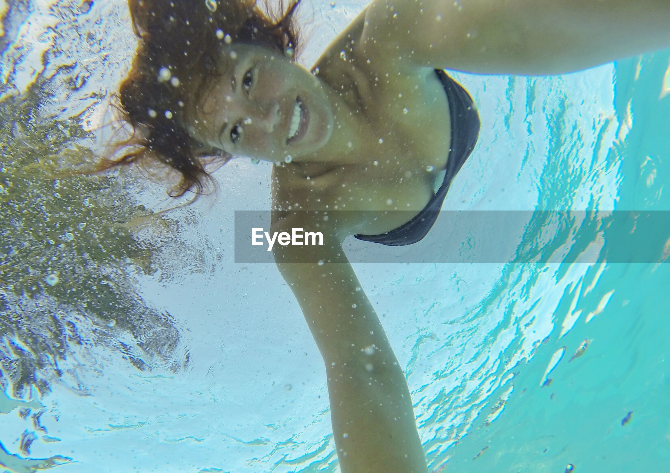 Low angle portrait of smiling woman swimming undersea