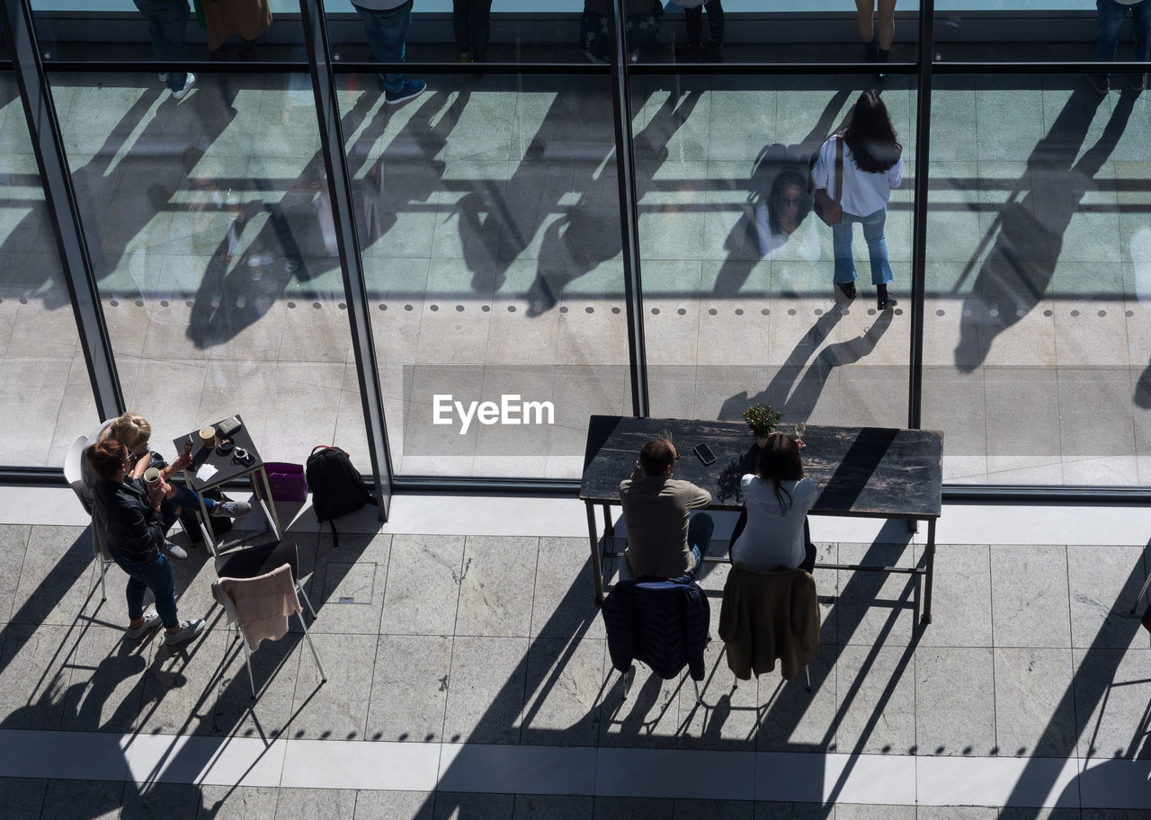 High Angle View Of People Sitting At Window In Modern Building