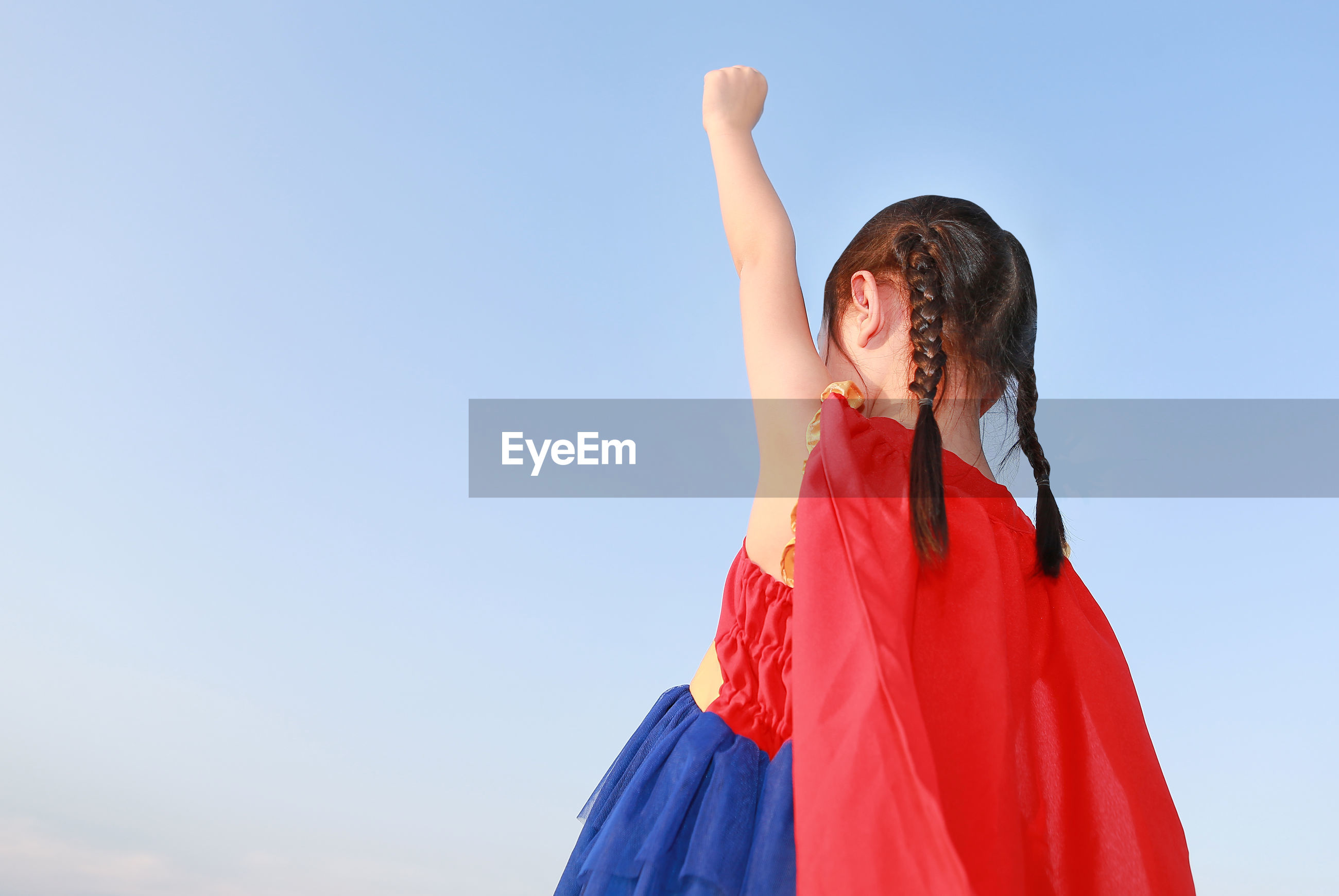 Low angle view of girl with hand raised standing against clear blue sky