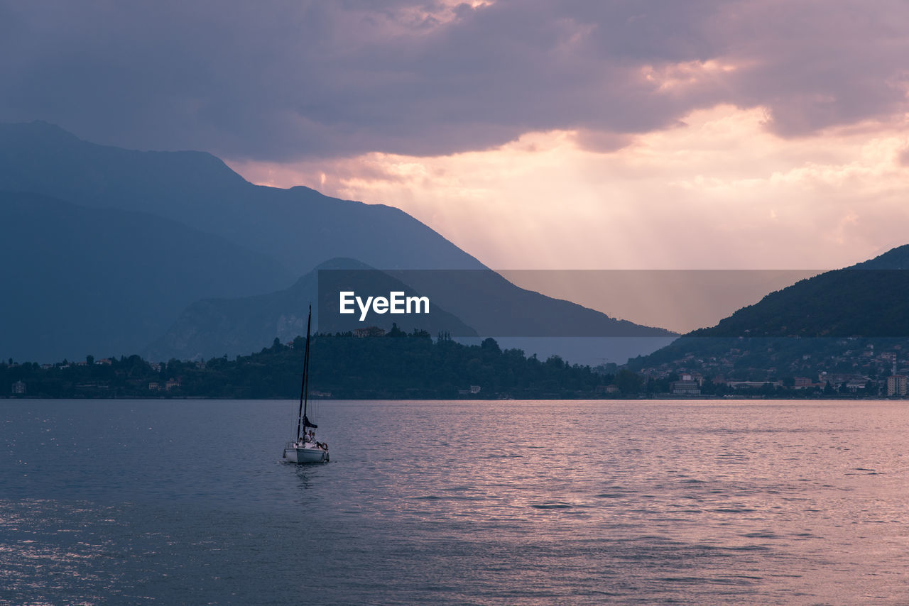 mountain, nautical vessel, water, sky, mode of transportation, scenics - nature, transportation, beauty in nature, sailboat, mountain range, cloud - sky, tranquil scene, tranquility, waterfront, sea, non-urban scene, nature, idyllic, no people, outdoors, yacht, yachting