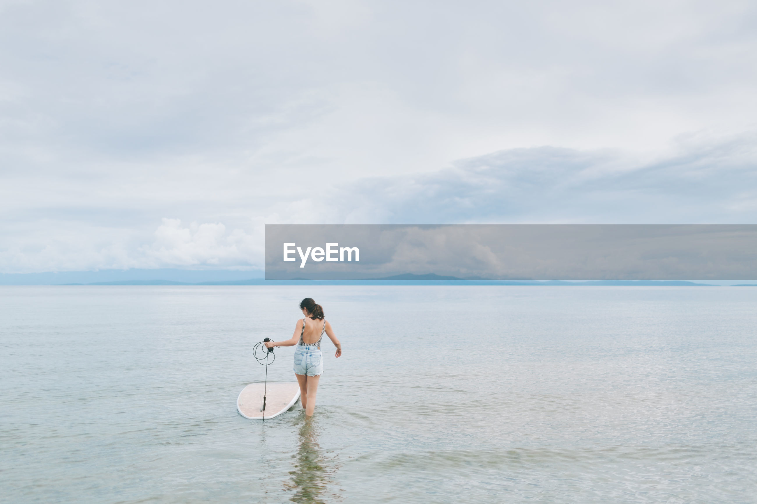 Rear view of woman with paddleboard walking at beach against sky