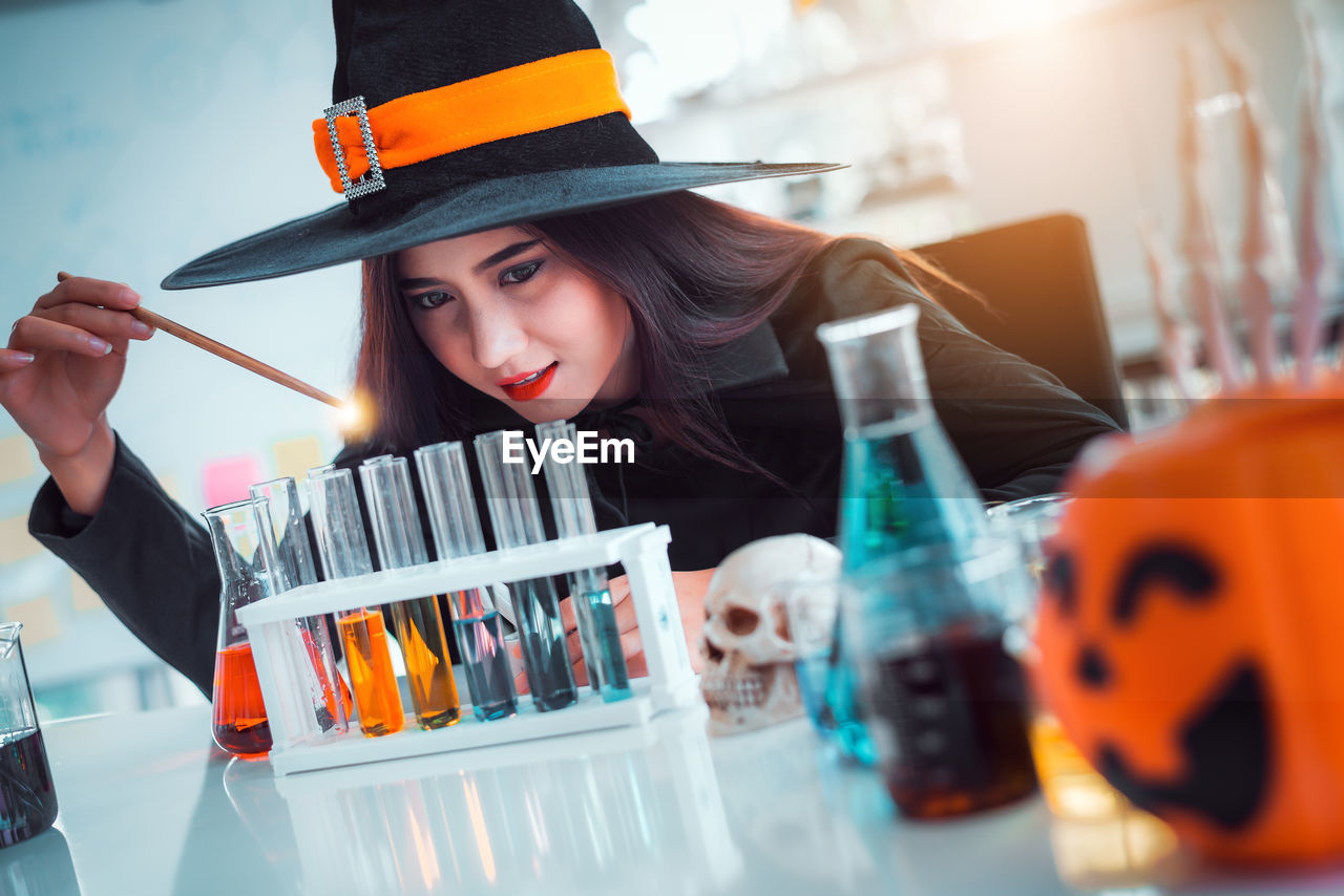 real people, one person, portrait, front view, young adult, young women, indoors, holding, leisure activity, headshot, lifestyles, women, selective focus, waist up, looking, beauty, orange color, hat, glass