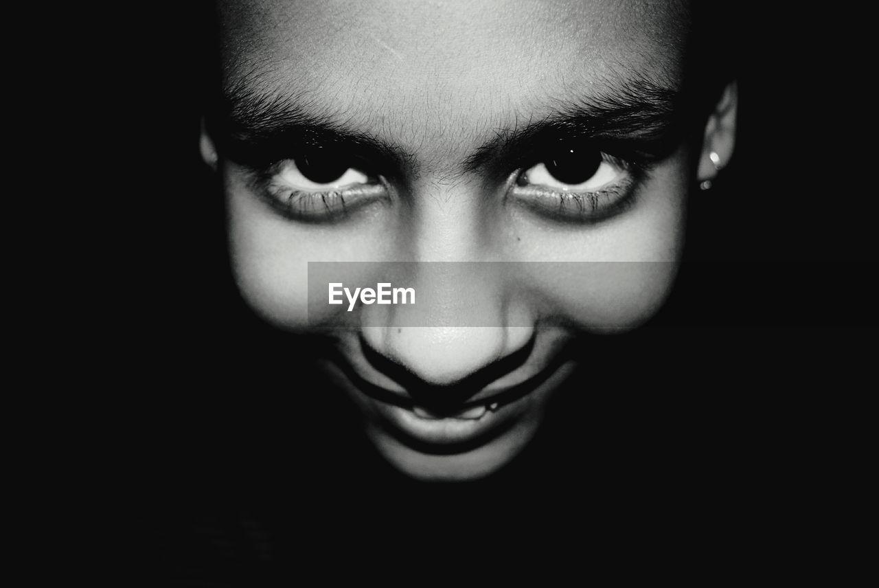 Close-Up Portrait Of Smiling Girl In Darkroom