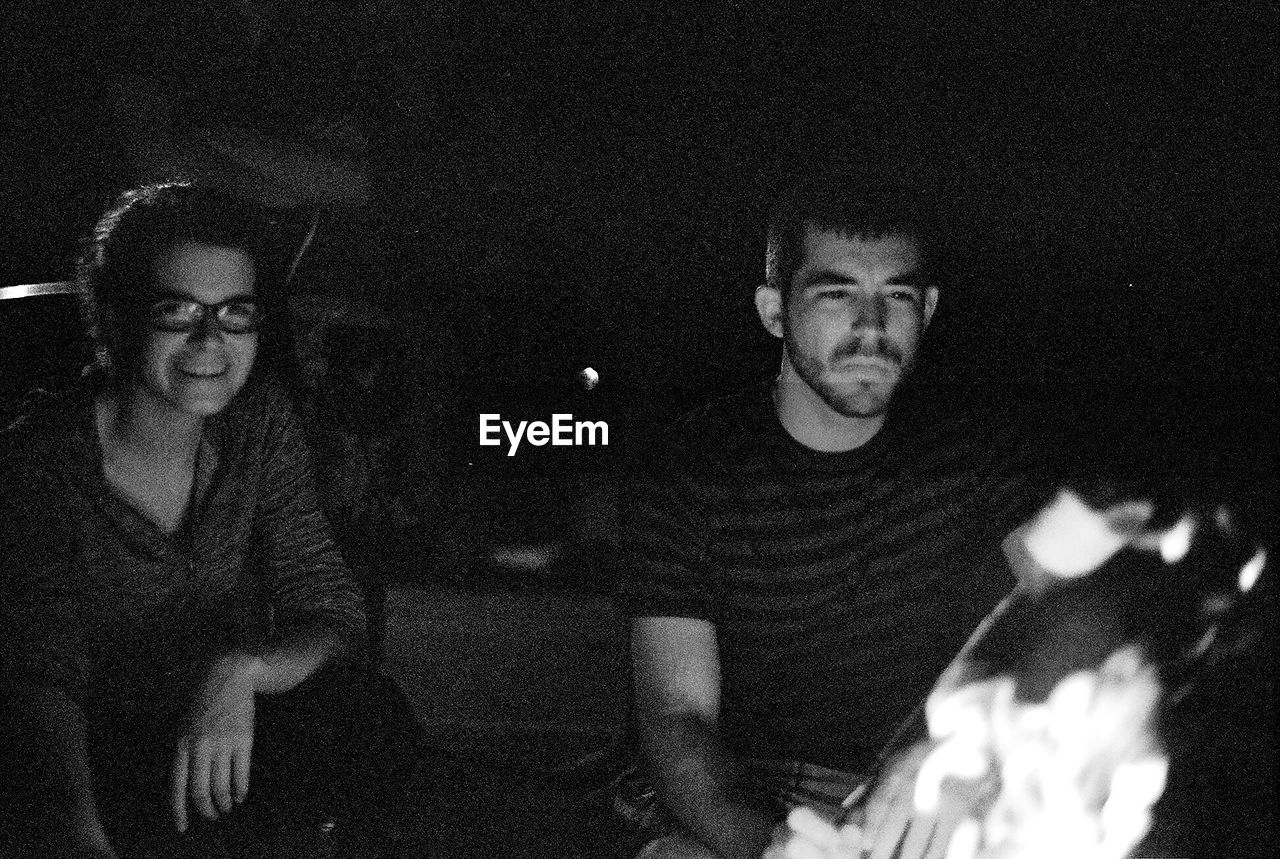 two people, night, portrait, real people, young adult, eyeglasses, glasses, young men, lifestyles, leisure activity, looking at camera, togetherness, people, men, young women, adult, waist up, front view, indoors, couple - relationship, nightlife