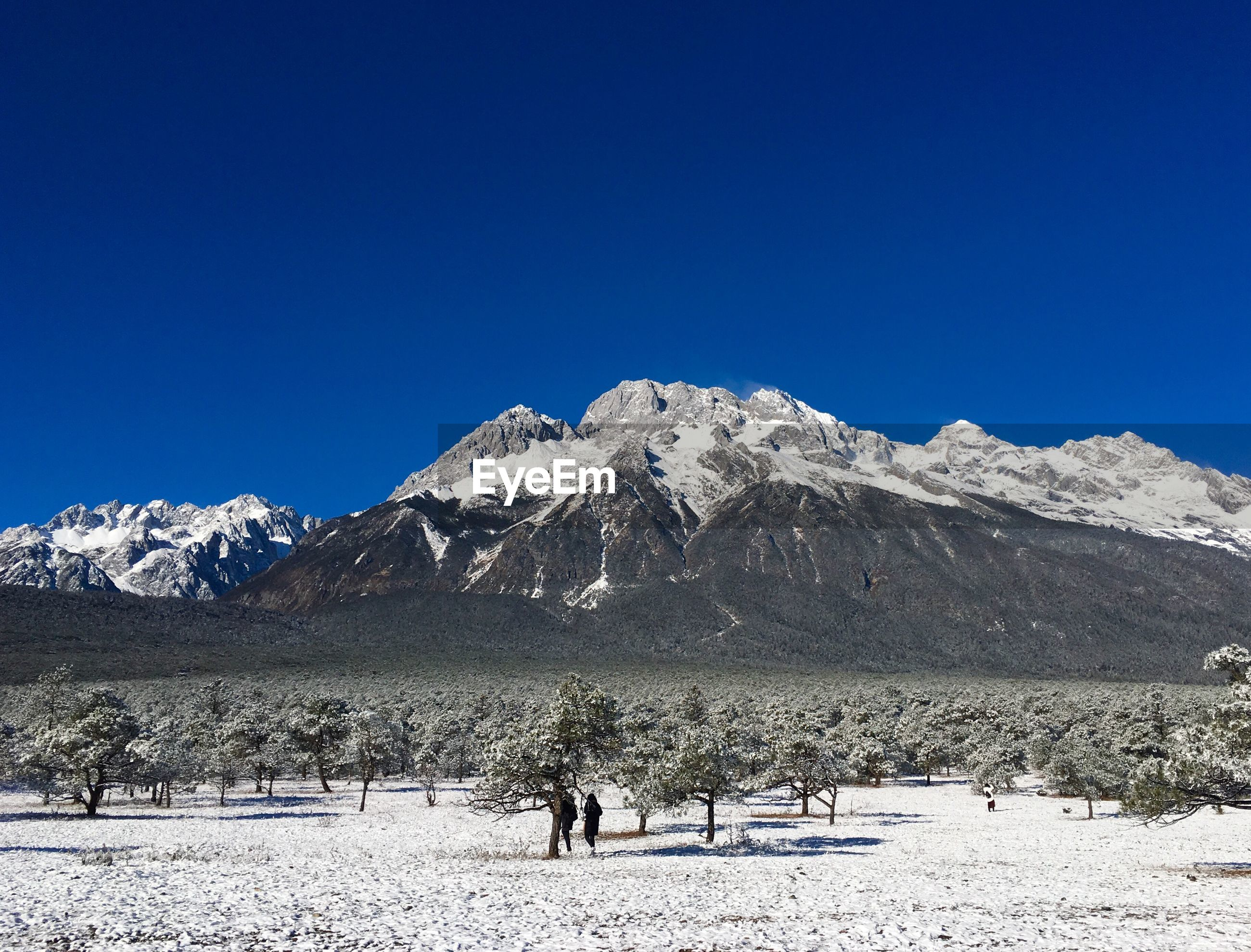 PEOPLE WALKING ON SNOWCAPPED MOUNTAIN AGAINST CLEAR BLUE SKY