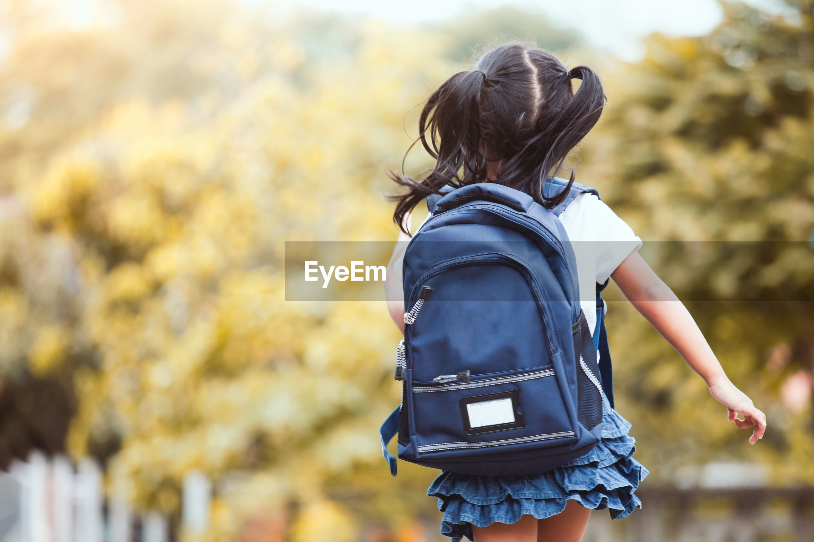 Rear view of girl wearing backpack while walking against trees