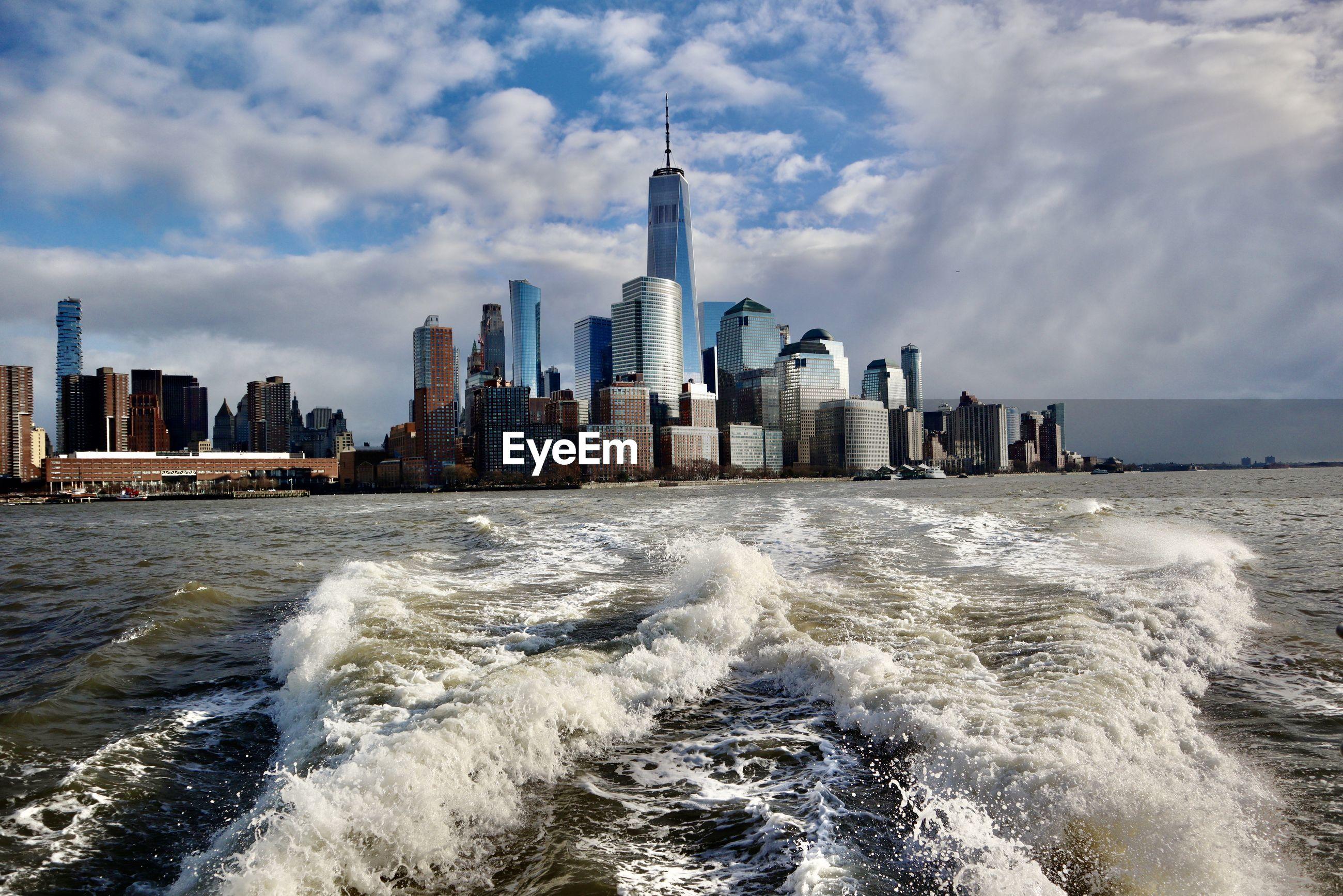 PANORAMIC SHOT OF SEA BY BUILDINGS AGAINST SKY