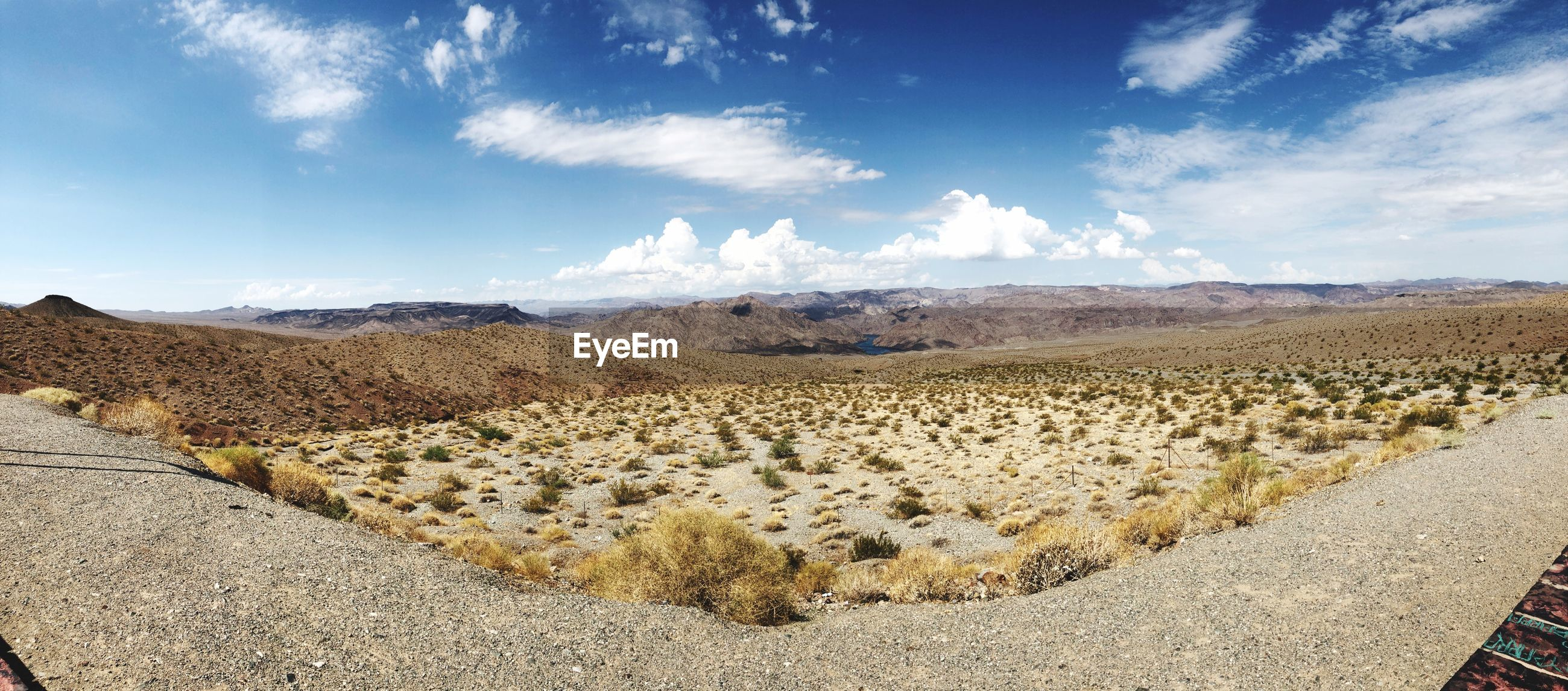 PANORAMIC VIEW OF ROAD AMIDST DESERT AGAINST SKY