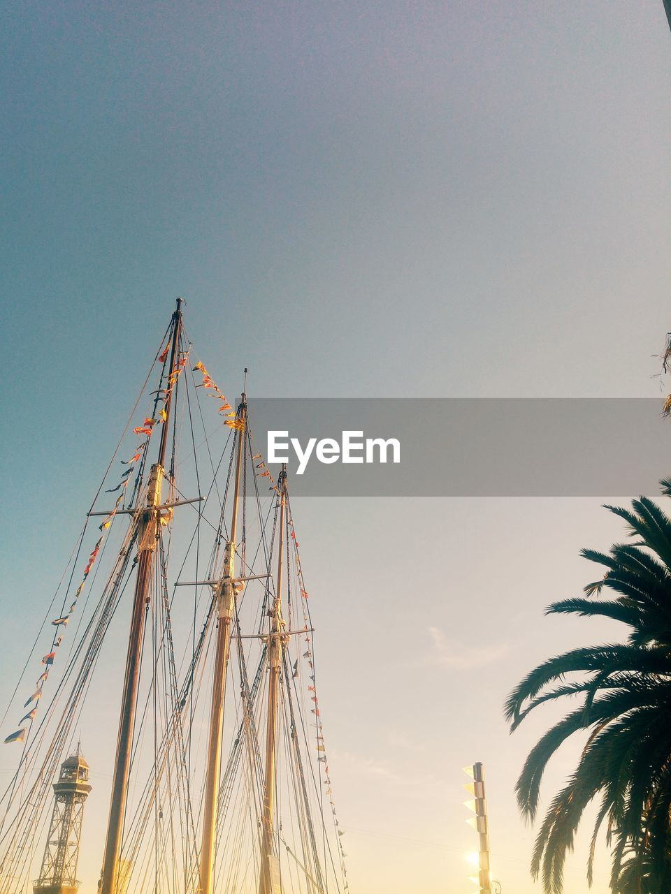 sky, sailboat, nautical vessel, transportation, mode of transportation, nature, mast, pole, no people, low angle view, water, sunset, sea, ship, copy space, clear sky, outdoors, harbor, tree, sailing, rigging