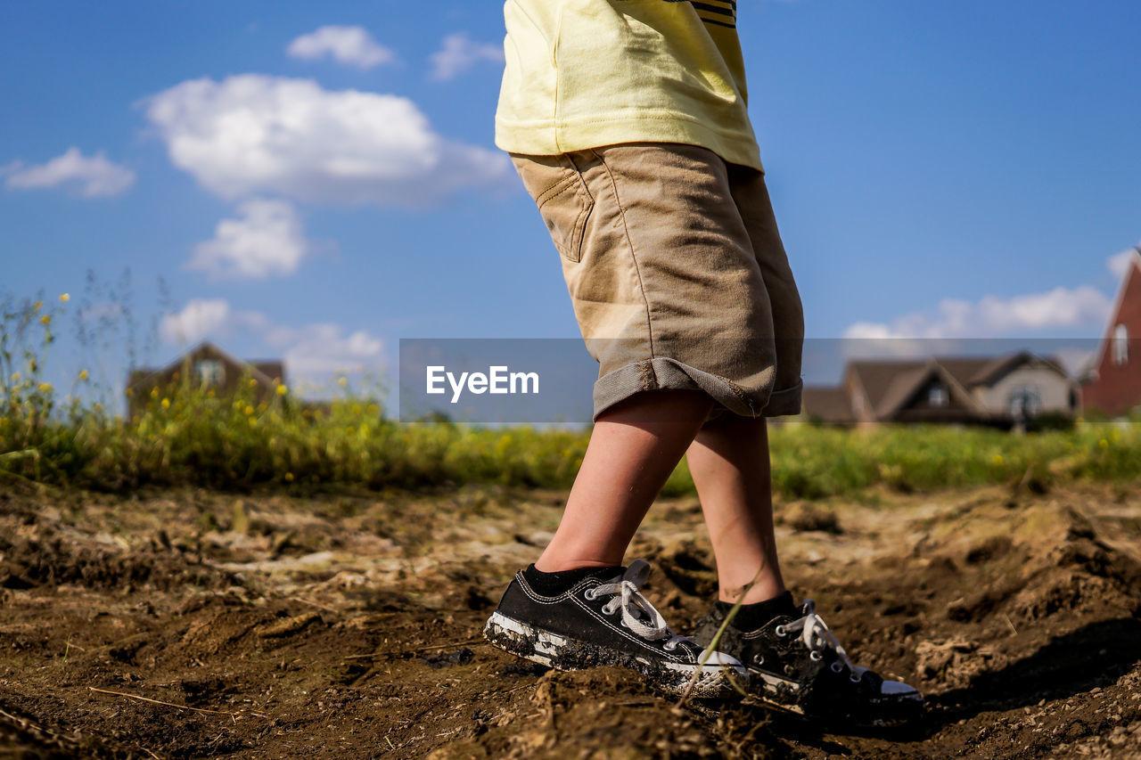 Low section of boy walking on field