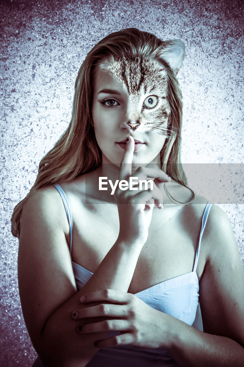 Digital composite image of young woman wearing cat mask showing silence gesture against wall