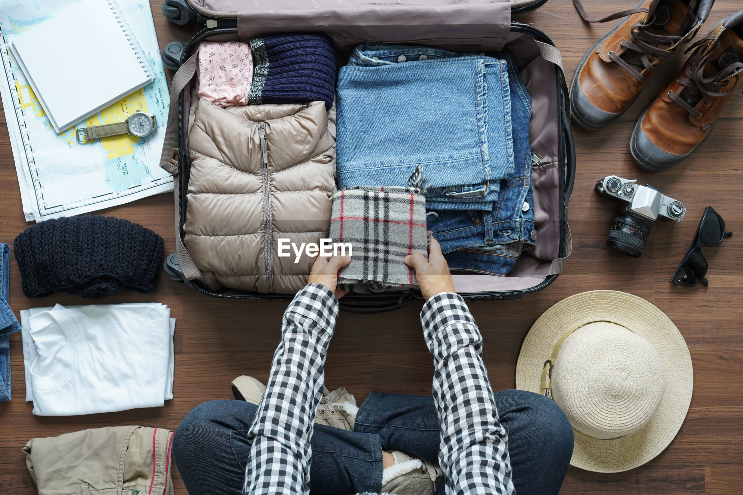 High angle view of man packing luggage at home