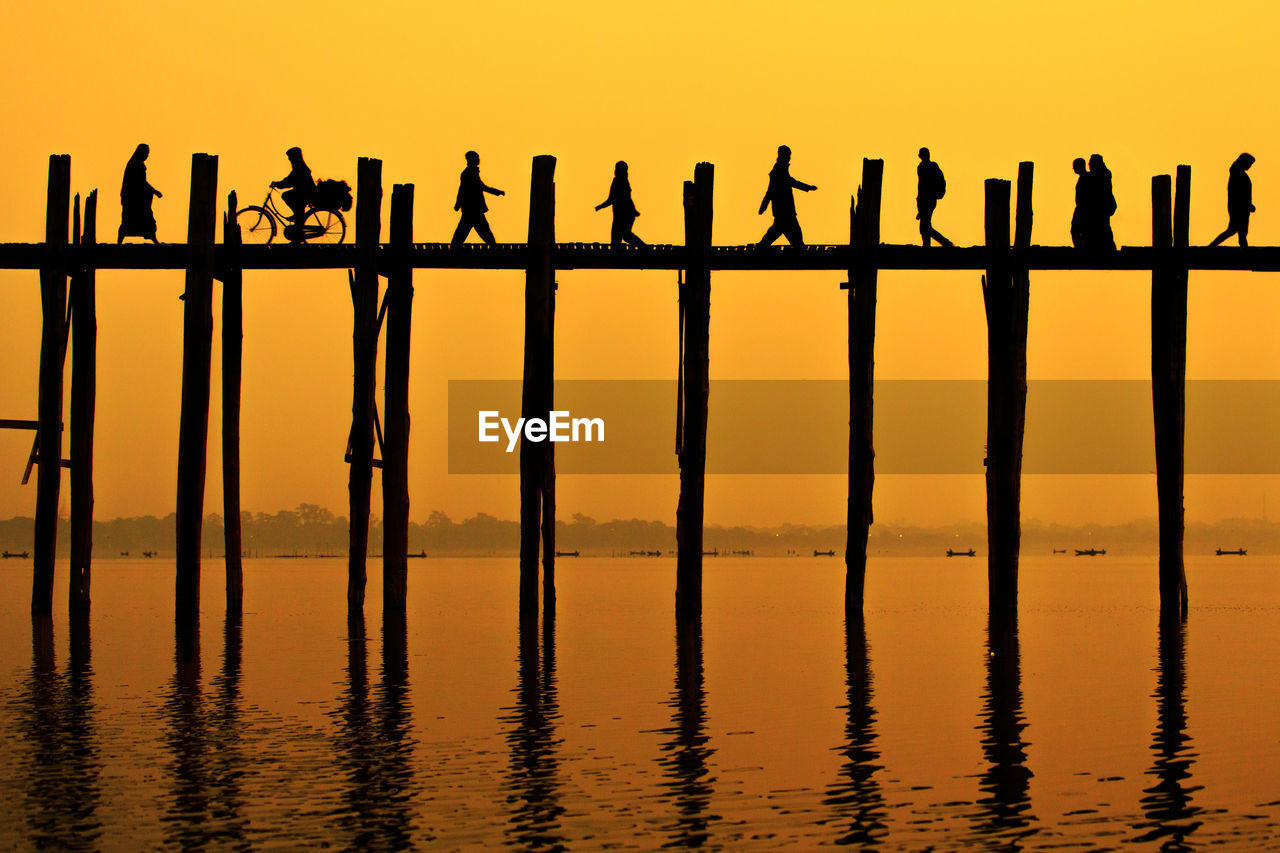 Low Angle View Of Silhouette People Walking On Pier Over River At Dawn