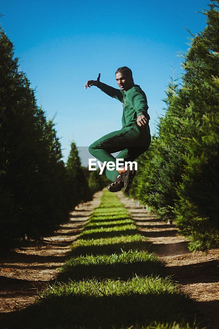 Full length of man jumping over field against sky