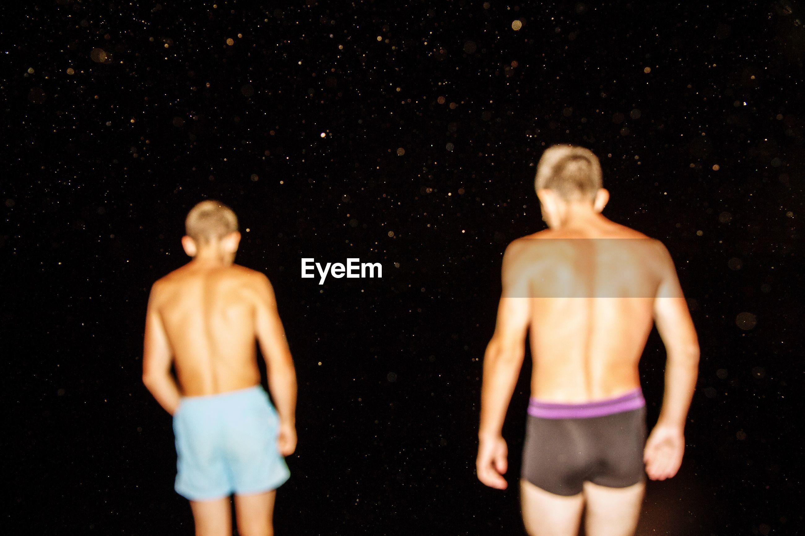 Rear view of shirtless friends standing against star field at night