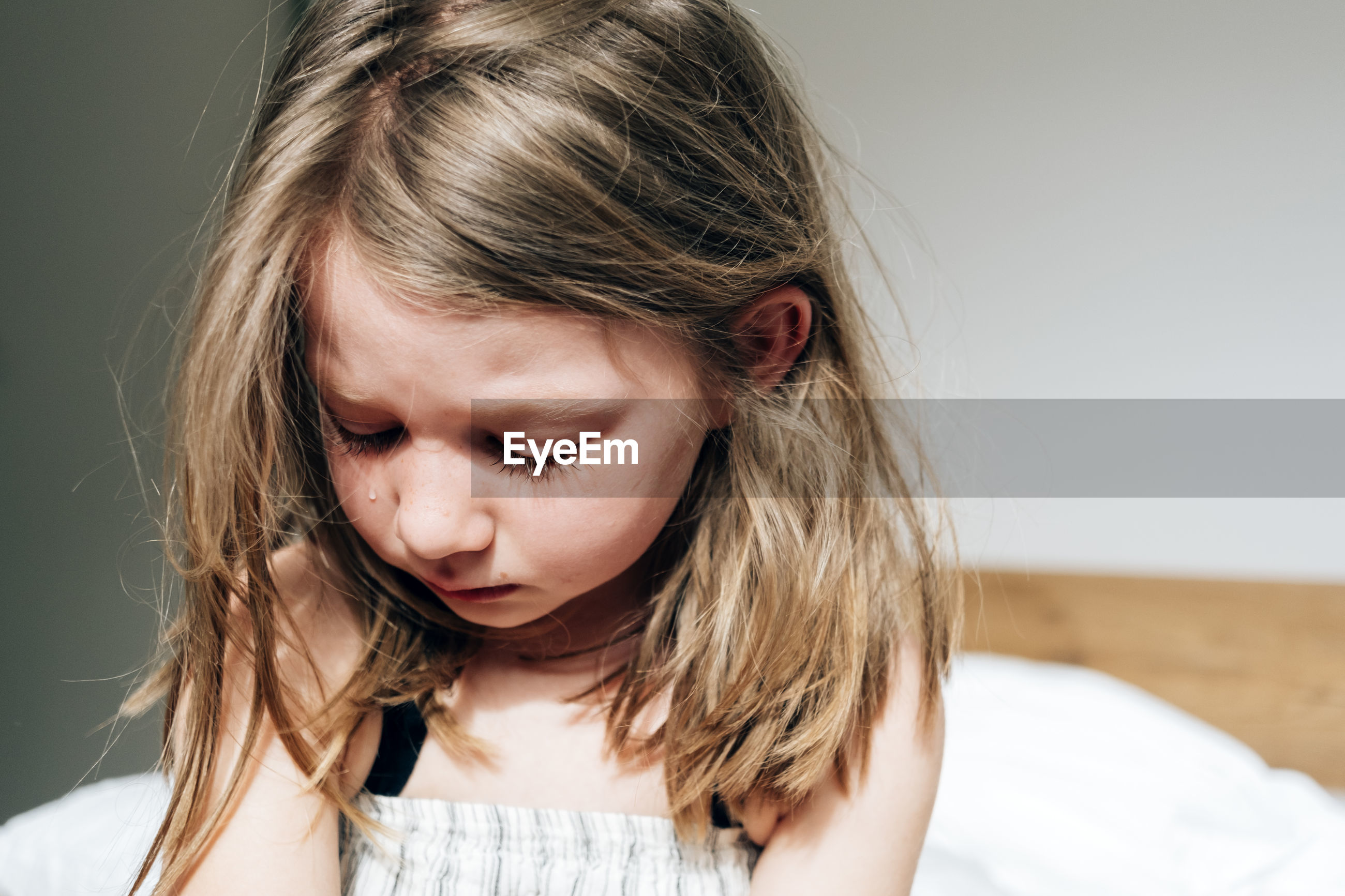 Close up portrait of a little girl at home crying sadly - lockdown sadness concept