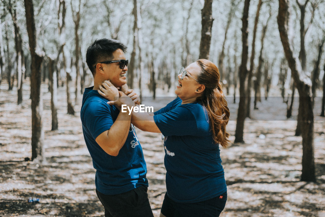 tree, young adult, standing, casual clothing, real people, two people, togetherness, leisure activity, land, day, lifestyles, young men, focus on foreground, forest, plant, young women, adult, nature, bonding, men, outdoors, hairstyle