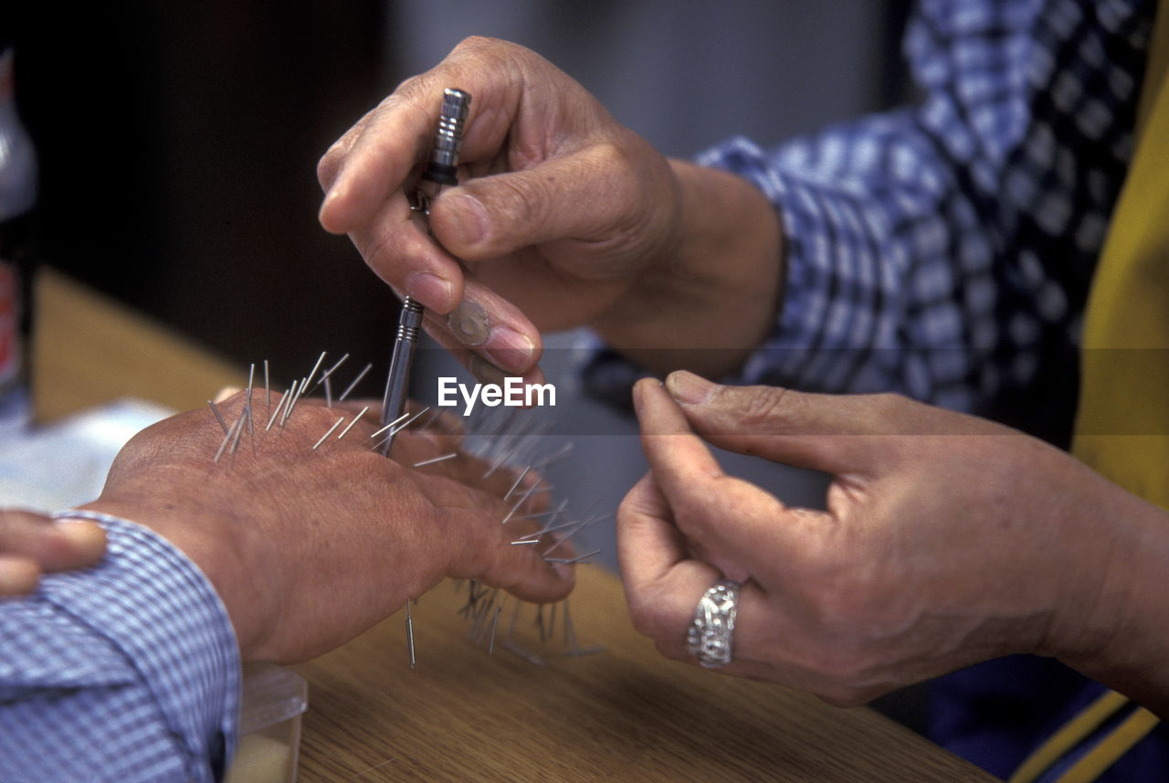 Midsection Of Man Piercing Nails On Human Hand