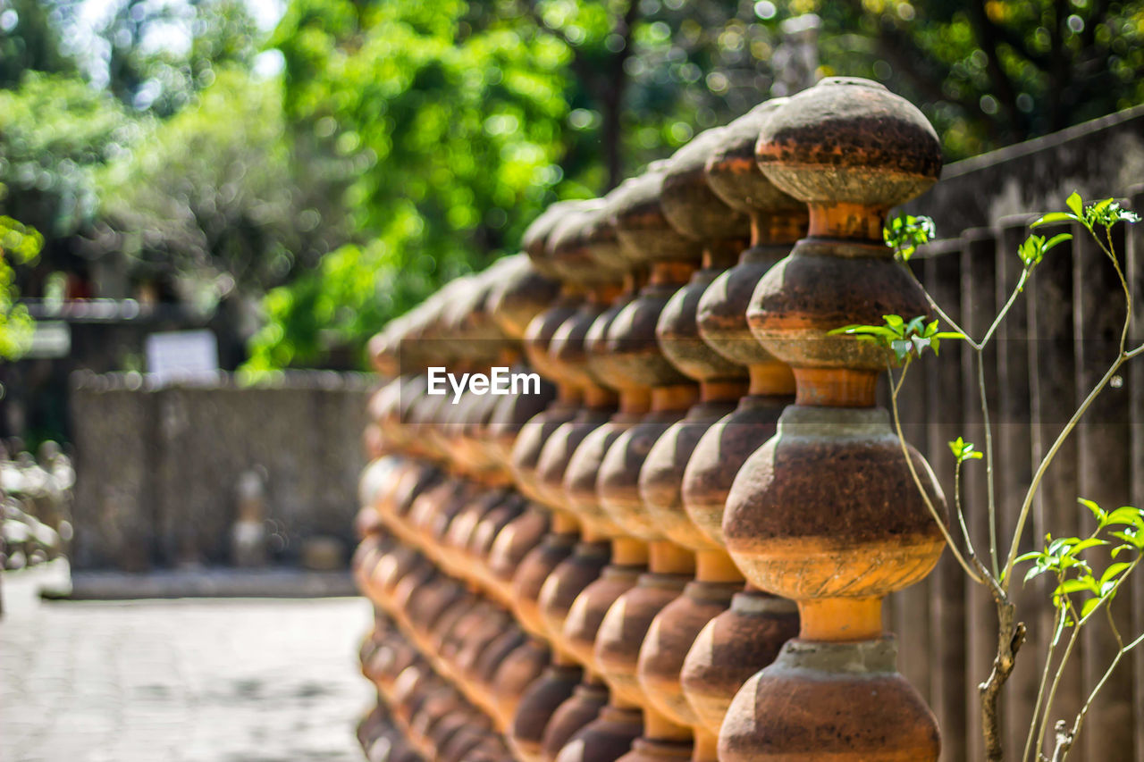 focus on foreground, no people, nature, day, plant, close-up, selective focus, architecture, tree, built structure, outdoors, stack, water, pattern, solid, creativity, sunlight, art and craft, stone material, sculpture