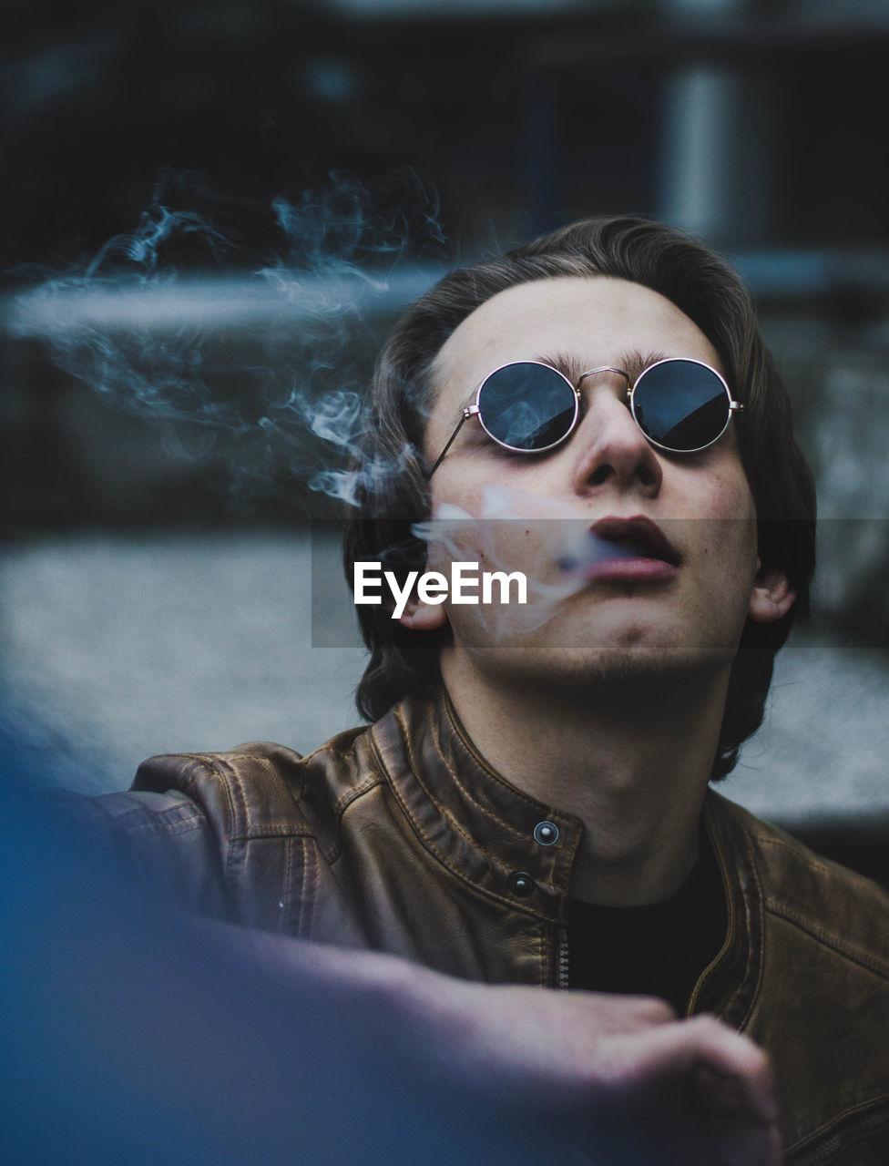 Close-up of man wearing sunglasses exhaling smoke