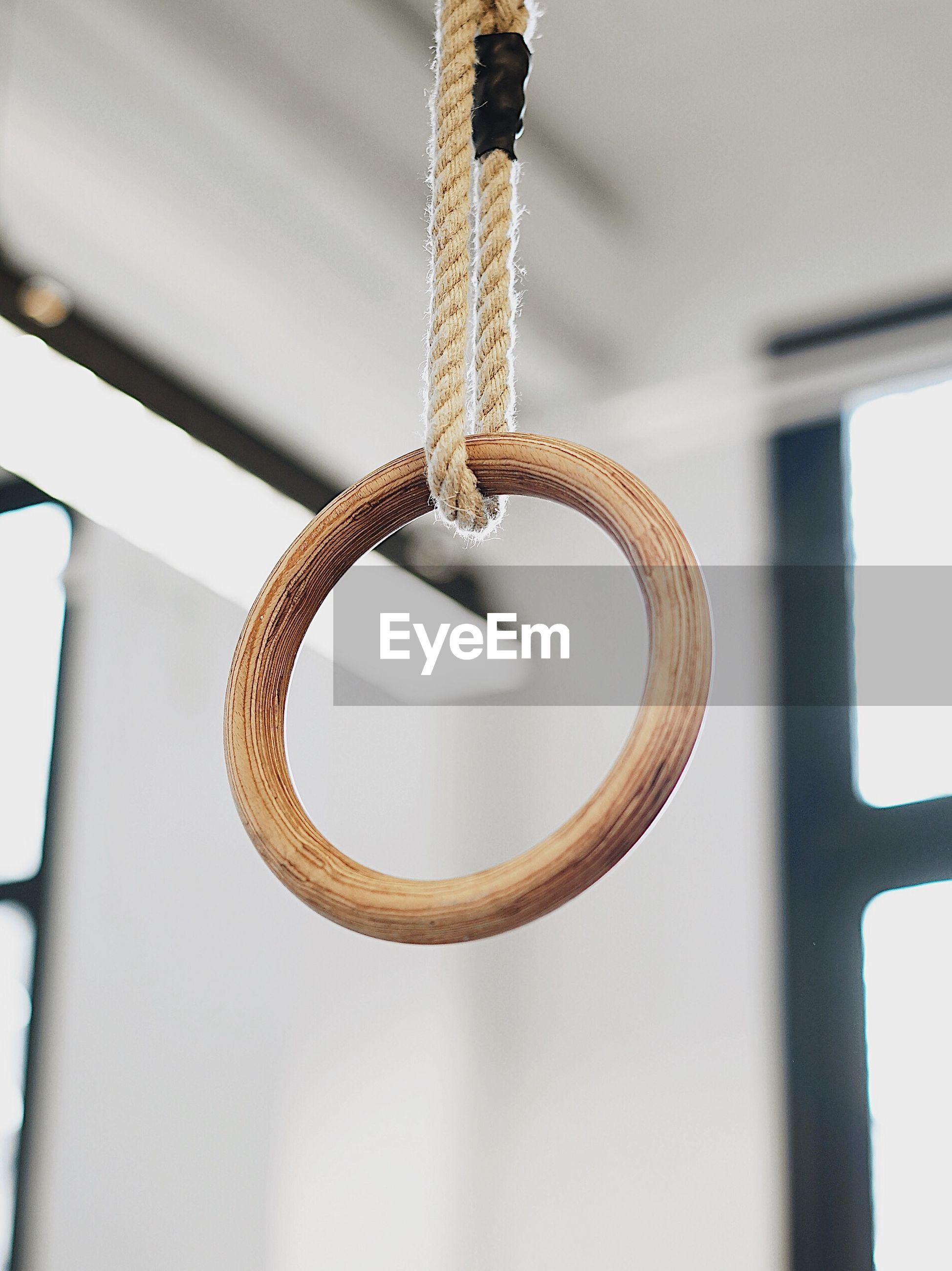 Close-up low angle view of gymnastic ring hanging in gym
