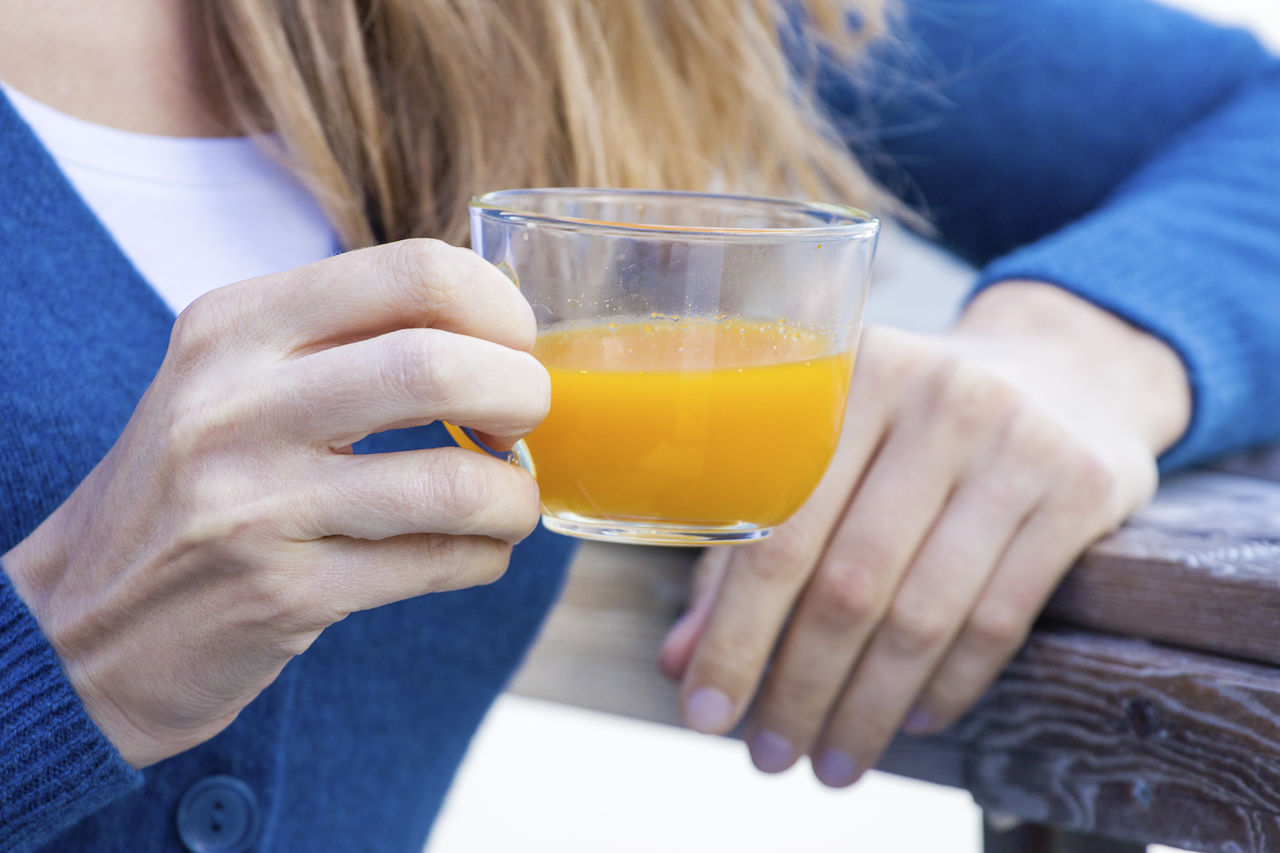 Midsection of woman drinking juice