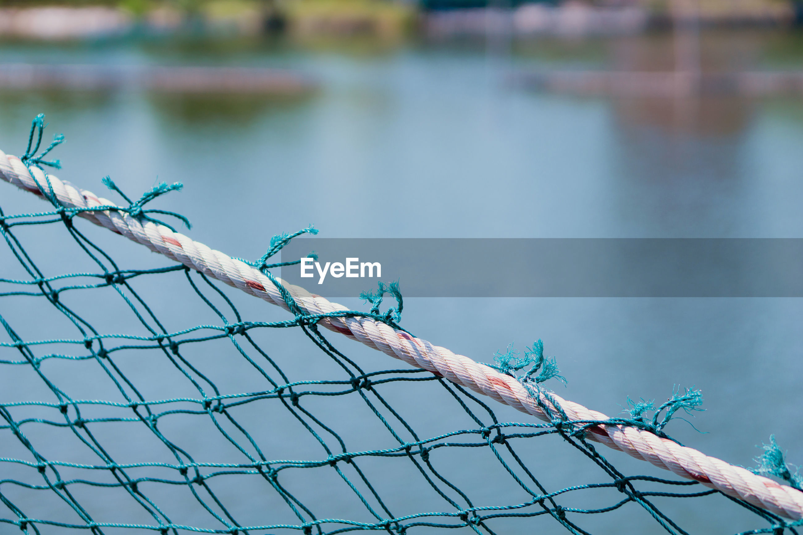 Close-up of barbed wire fence against blue sky