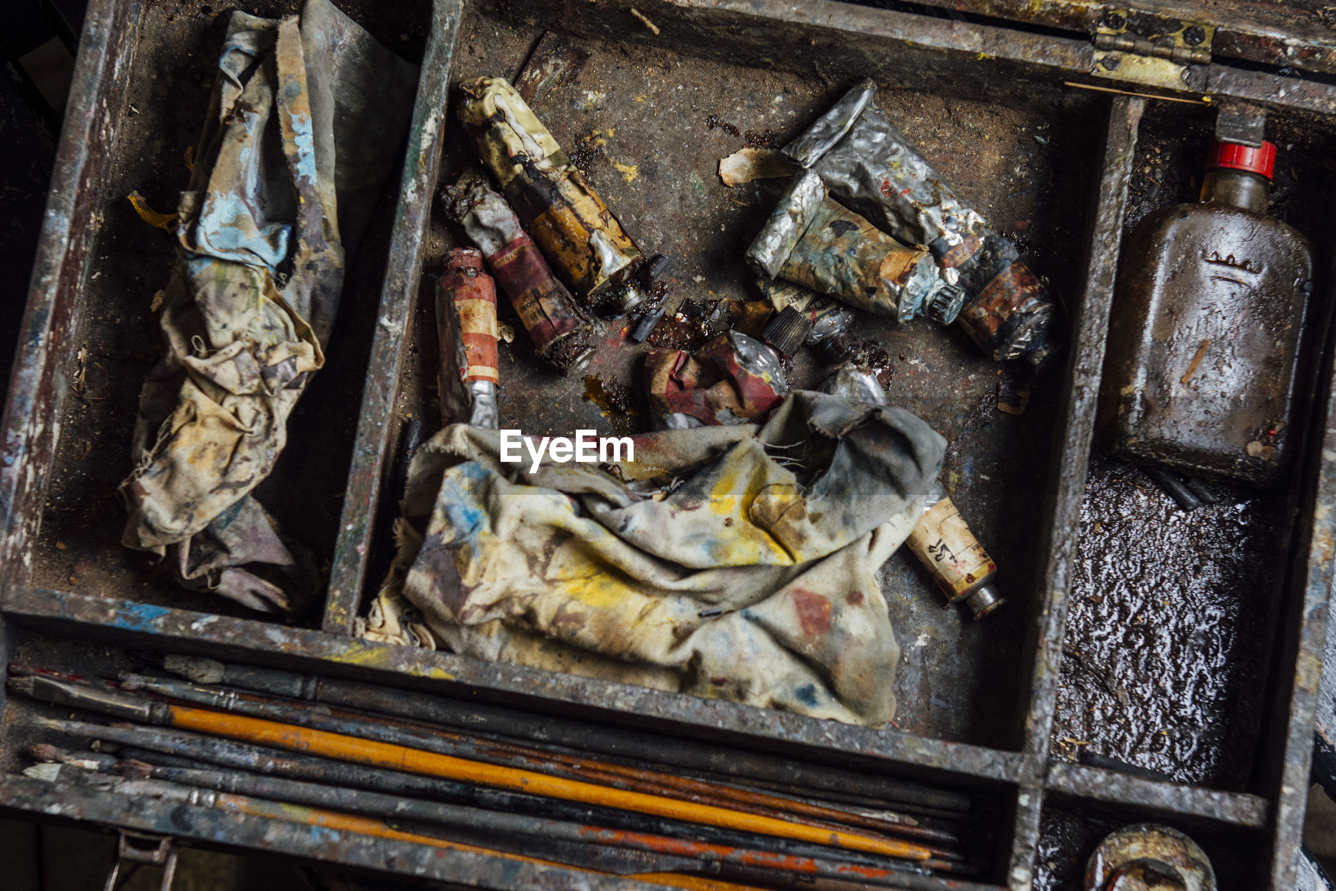 High angle view of paint tubes and brushes in abandoned box