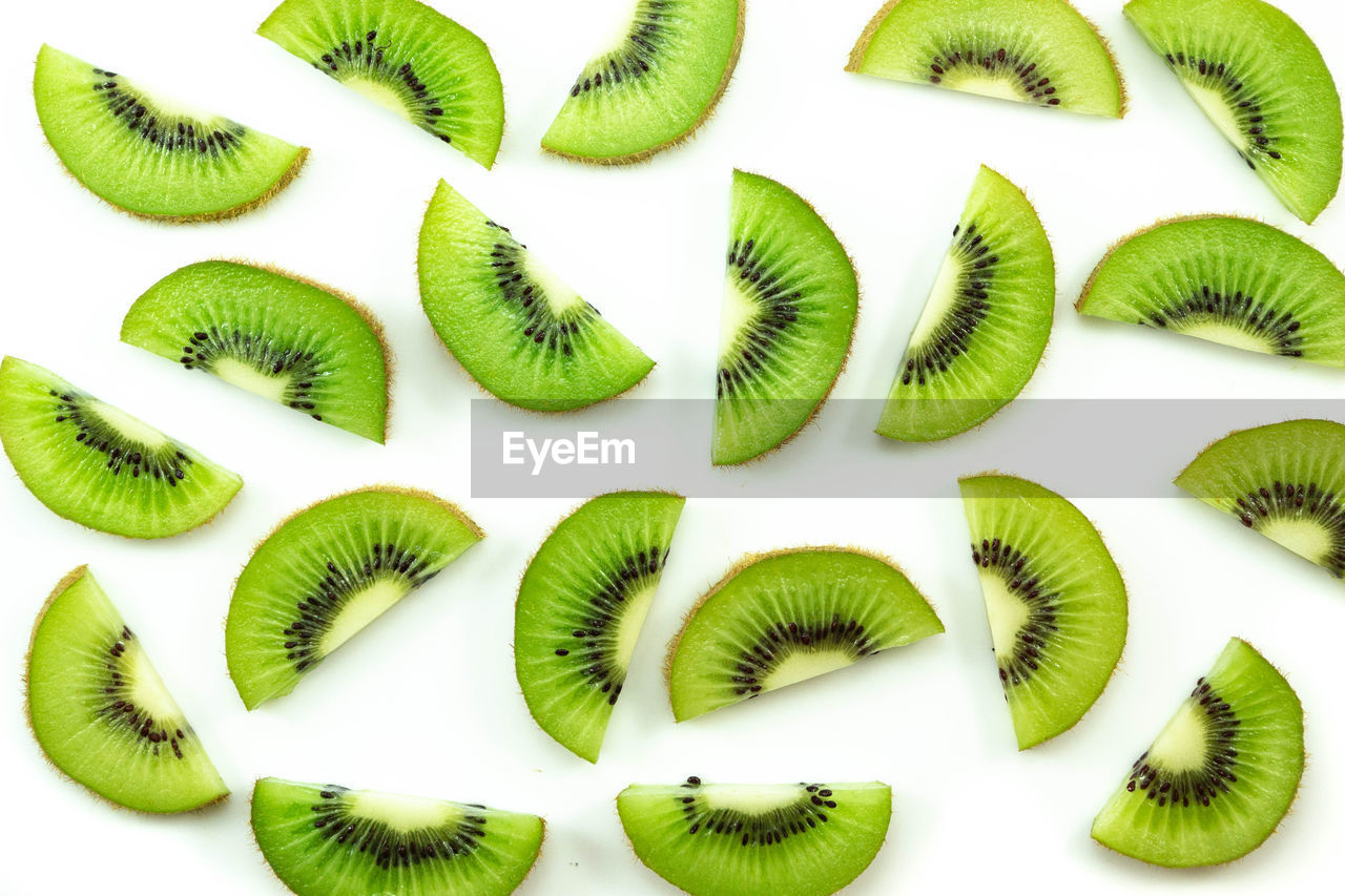 kiwi, green color, kiwi - fruit, white background, food and drink, freshness, indoors, food, close-up, healthy eating, no people, still life, slice, studio shot, group of objects, wellbeing, backgrounds, fruit, in a row, large group of objects, chopped