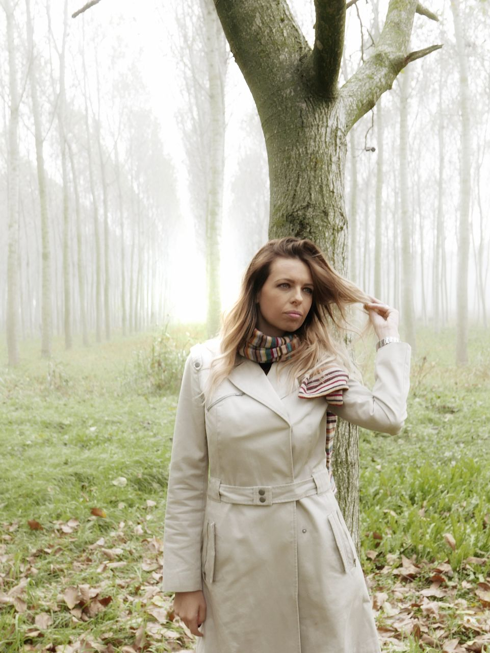 tree, young adult, one person, tree trunk, real people, young women, nature, three quarter length, front view, casual clothing, standing, leisure activity, day, outdoors, lifestyles, beautiful woman, grass, looking at camera, forest, smiling, branch, portrait, happiness, bare tree, people