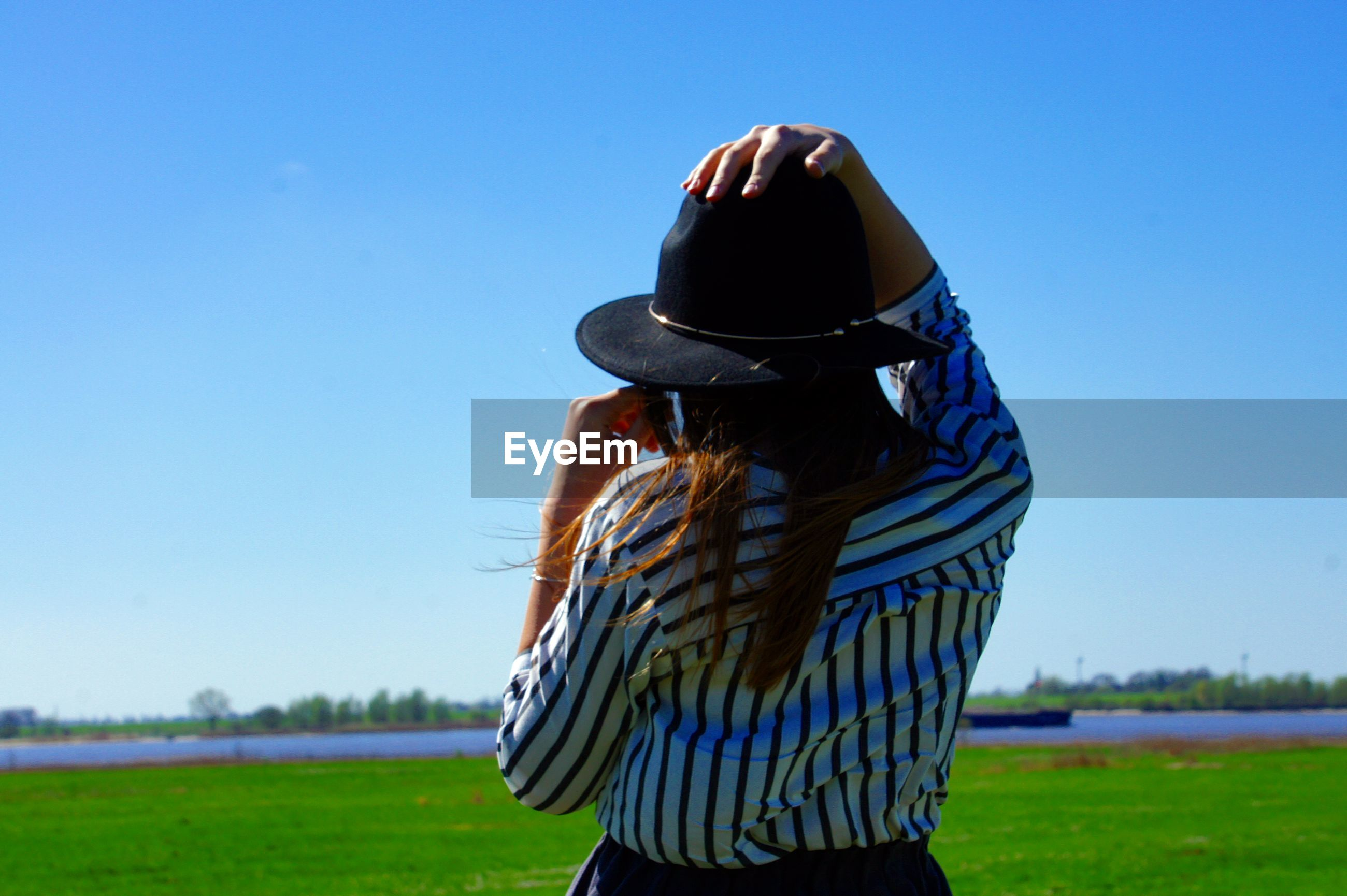 Rear view of woman standing on field against clear blue sky