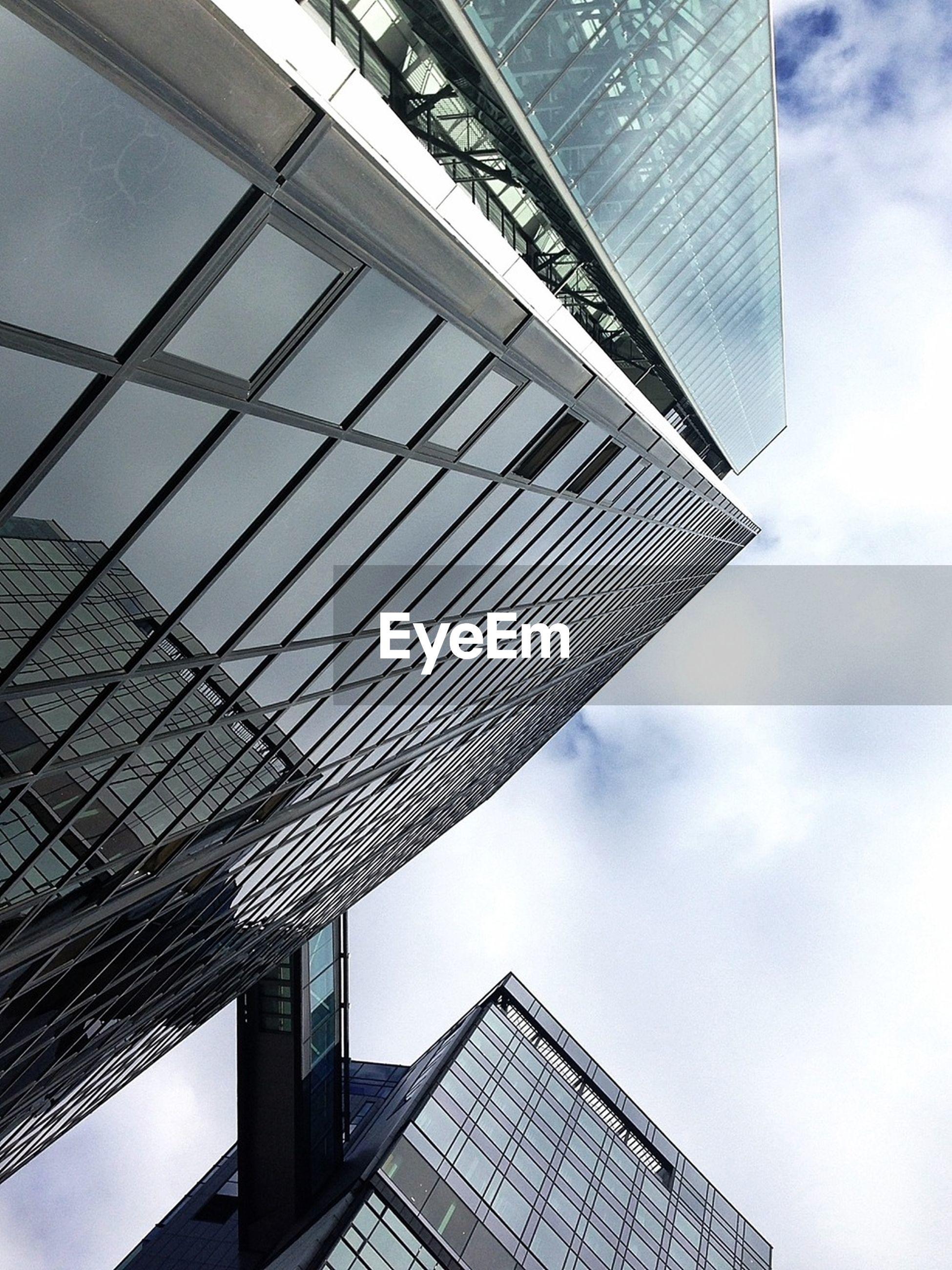 Directly below shot of modern buildings against cloudy sky