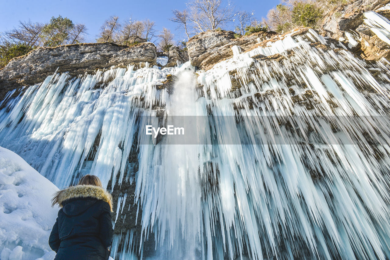 winter, cold temperature, waterfall, snow, motion, nature, long exposure, one person, real people, rear view, beauty in nature, leisure activity, outdoors, rock - object, blurred motion, day, scenics, low angle view, adventure, frozen, lifestyles, water, vacations, warm clothing, men, mountain, people