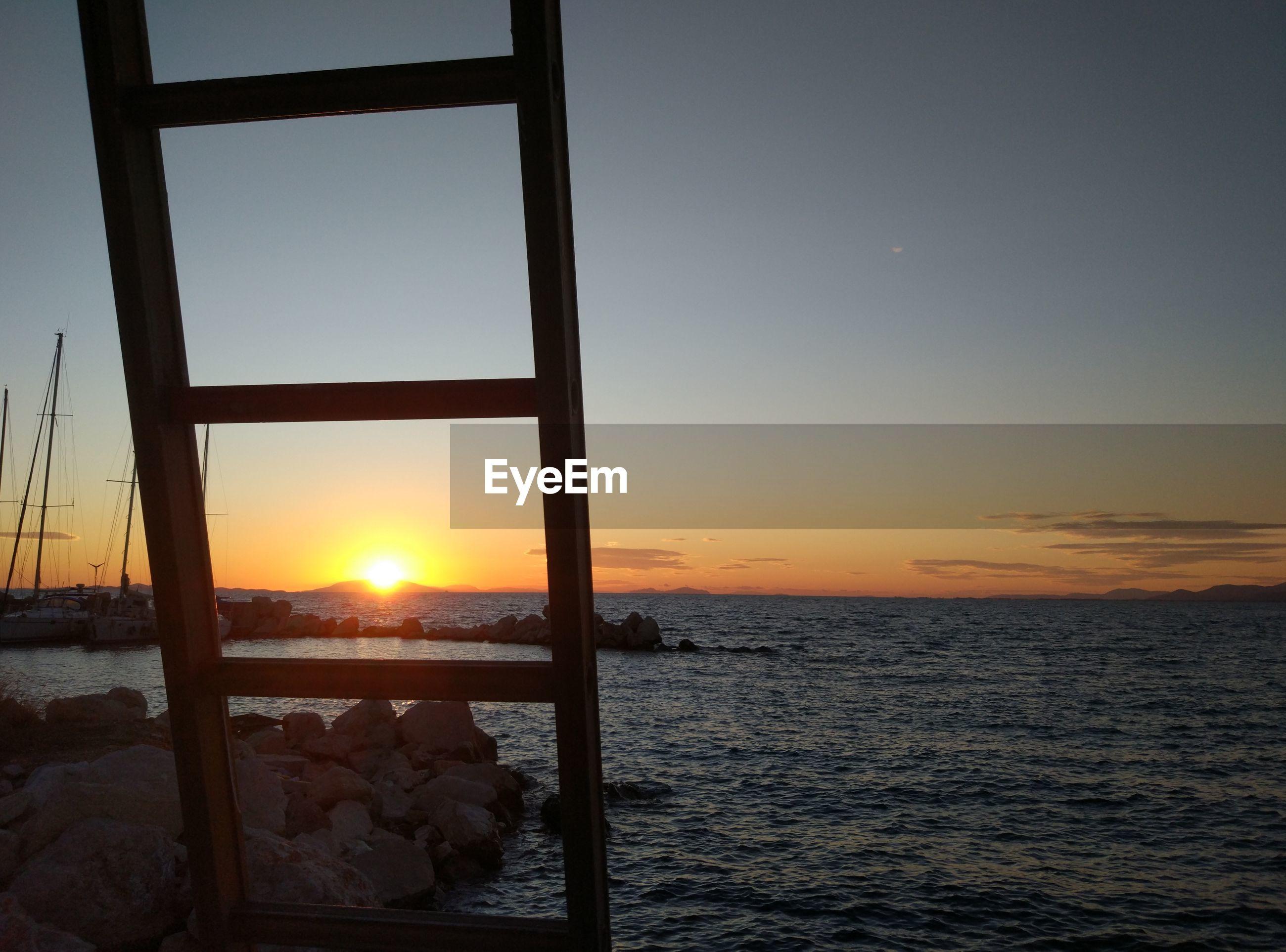 CLOSE-UP OF SEA AGAINST ORANGE SKY