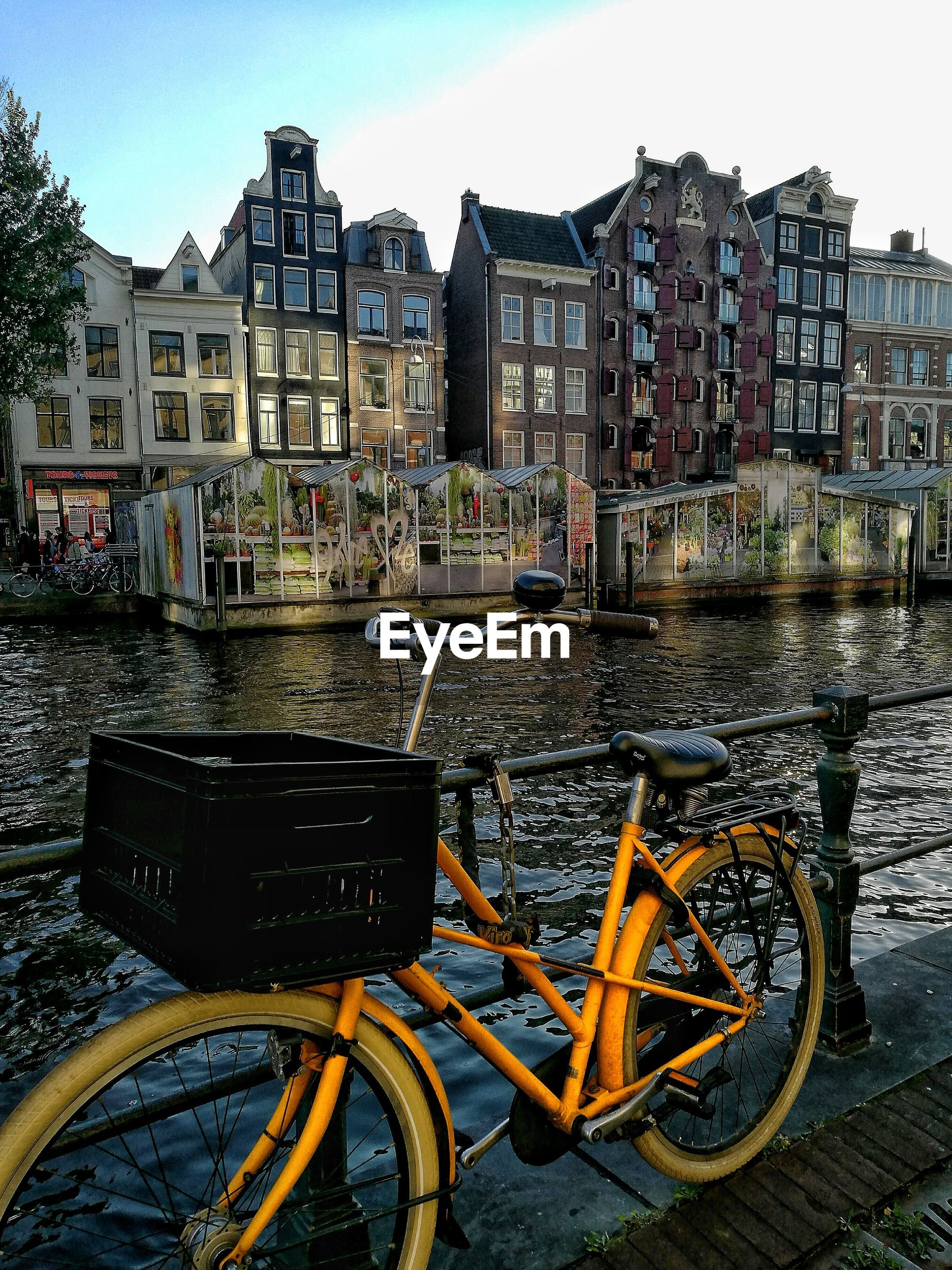 Bicycle parked by canal in city