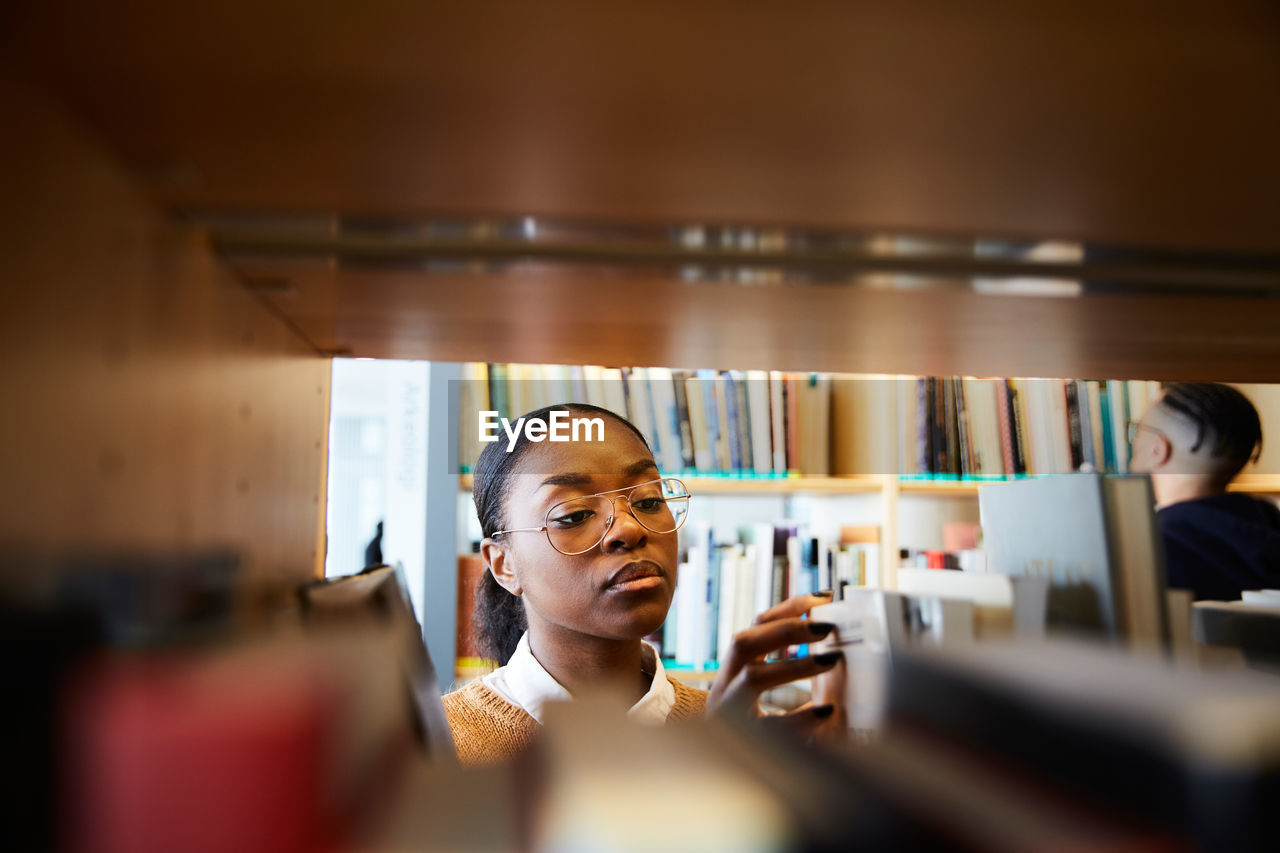 selective focus, indoors, women, real people, portrait, headshot, adult, young adult, one person, book, young women, lifestyles, females, shelf, smiling, working, standing, choice, bookshelf