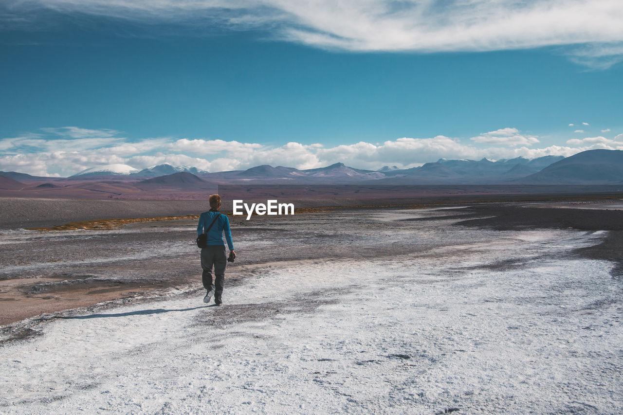 Rear View Of Man Walking On Landscape Against Sky