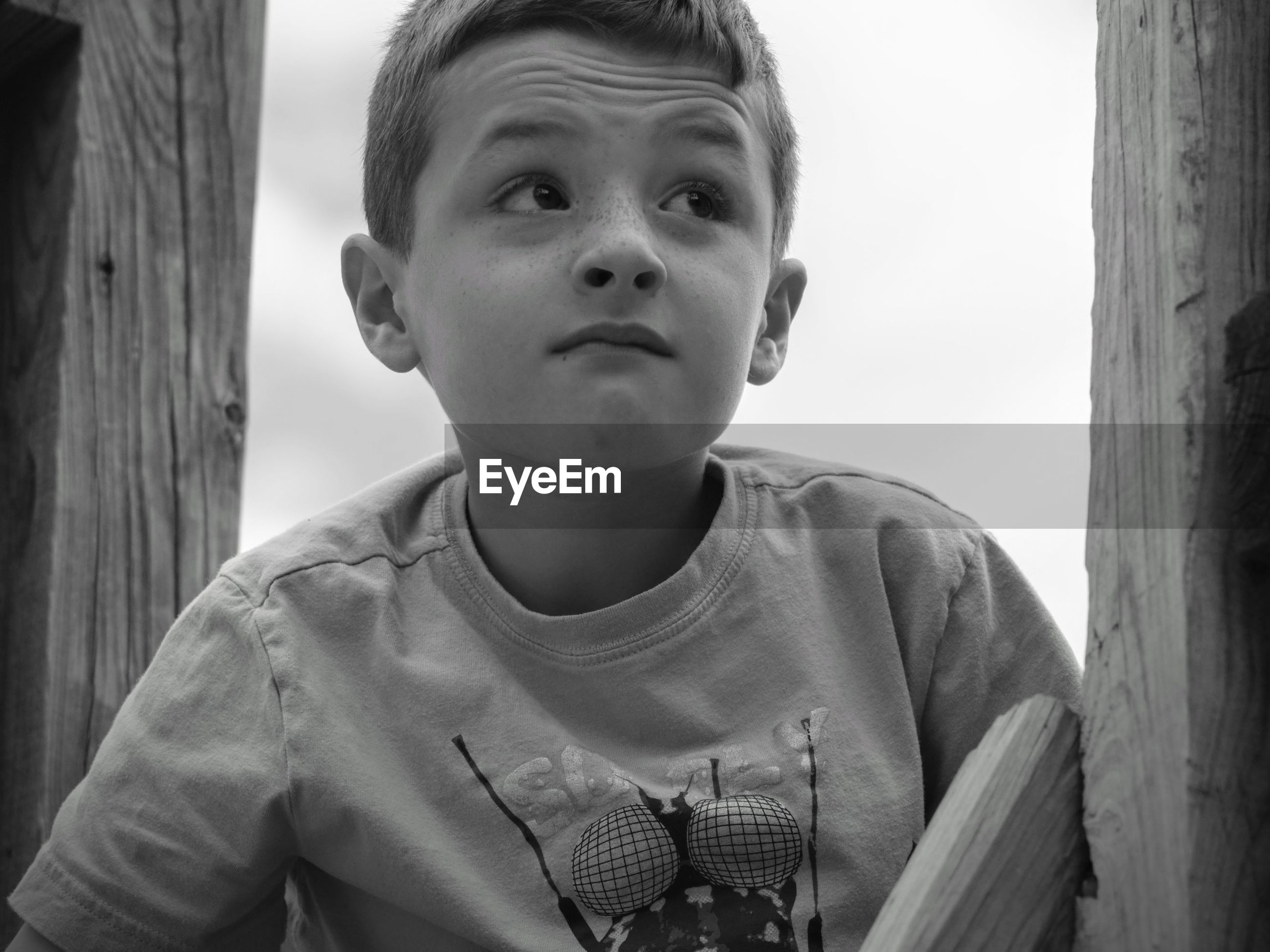 Close-up of boy making face by wooden post