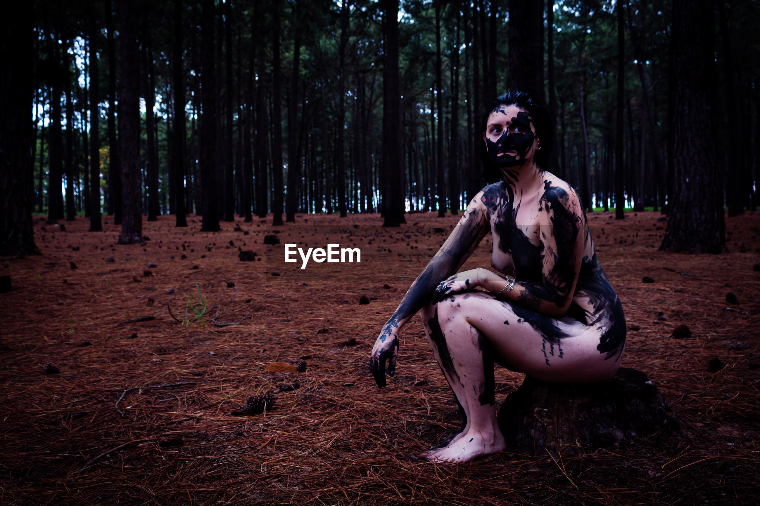 Naked woman covered with paint while sitting in forest