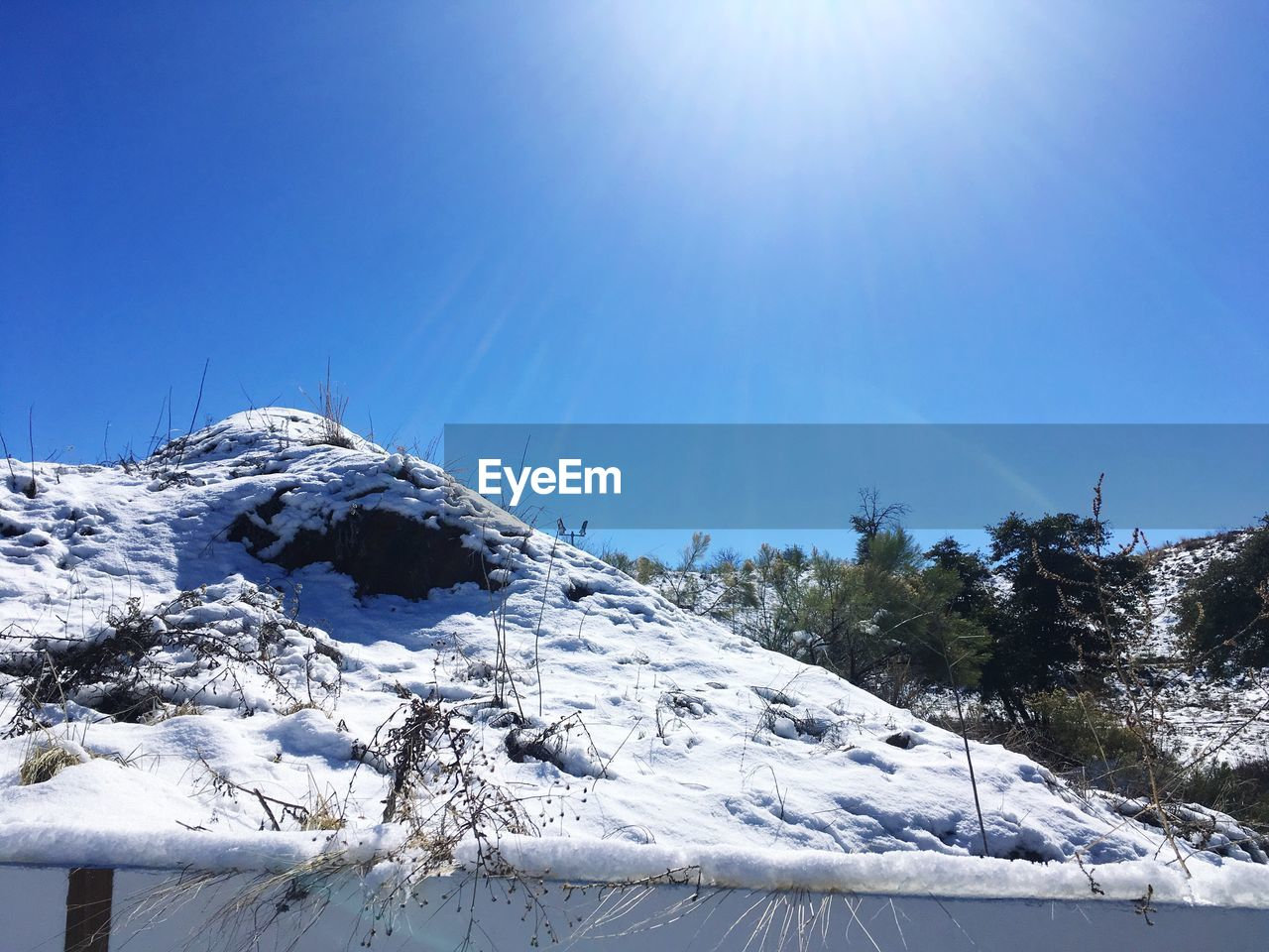snow, cold temperature, winter, sky, beauty in nature, mountain, tranquility, sunlight, clear sky, scenics - nature, tranquil scene, day, nature, covering, blue, snowcapped mountain, plant, no people, non-urban scene, bright, mountain peak