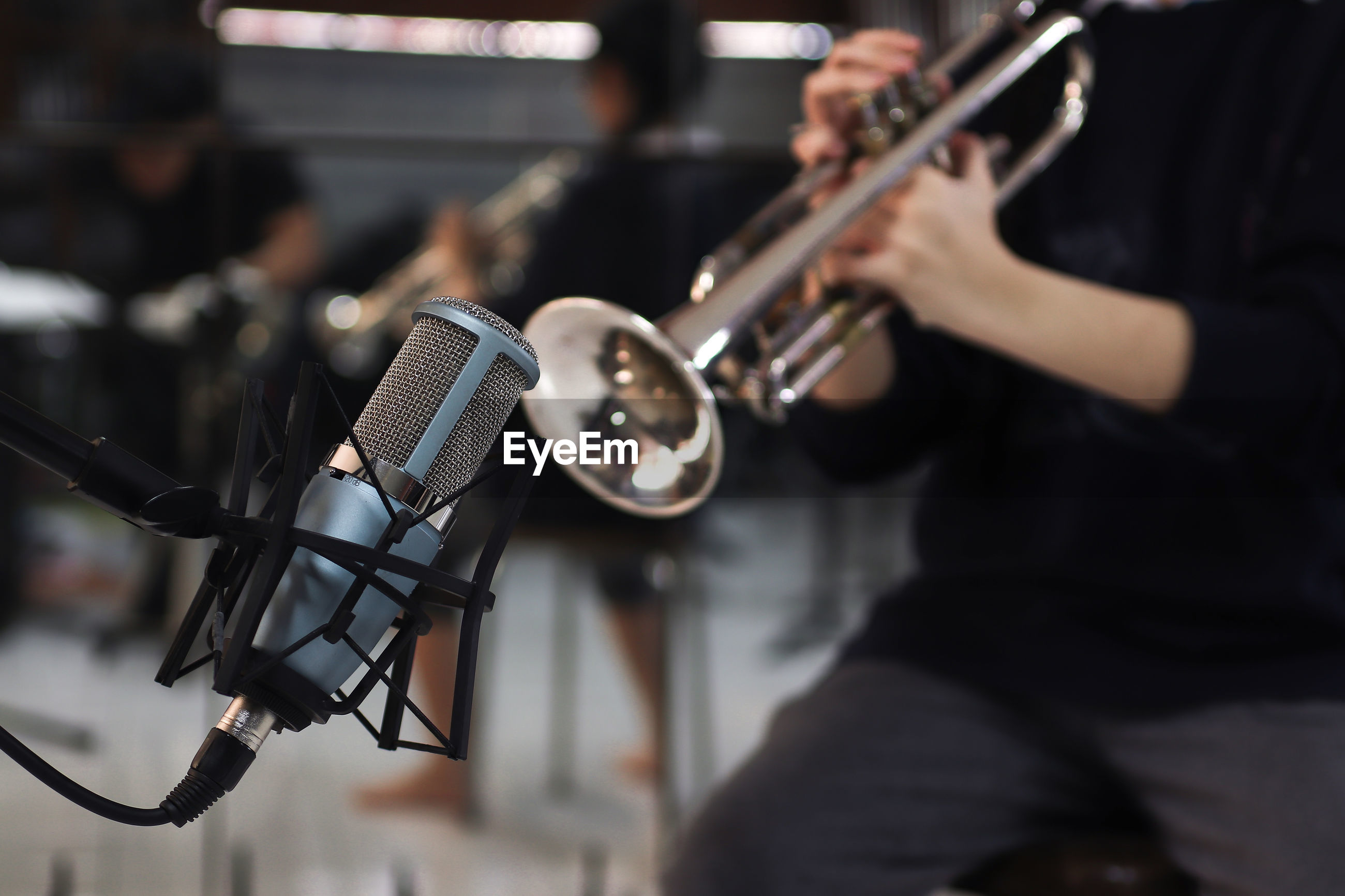 Midsection of man playing trumpet by microphone