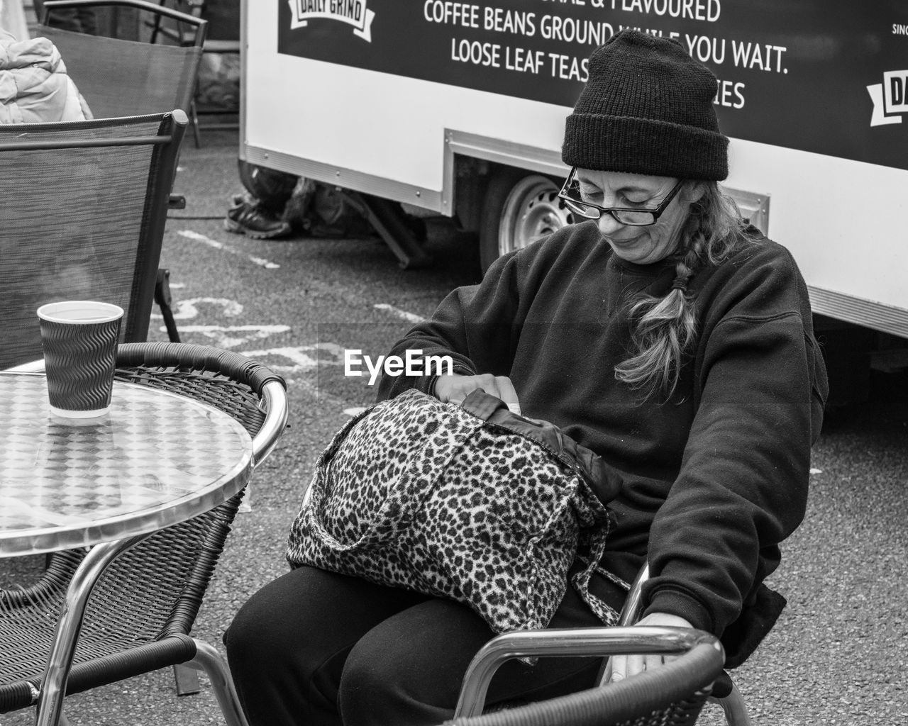 real people, sitting, one person, clothing, lifestyles, hat, seat, leisure activity, winter, casual clothing, chair, warm clothing, men, transportation, communication, food and drink, three quarter length, adult, women