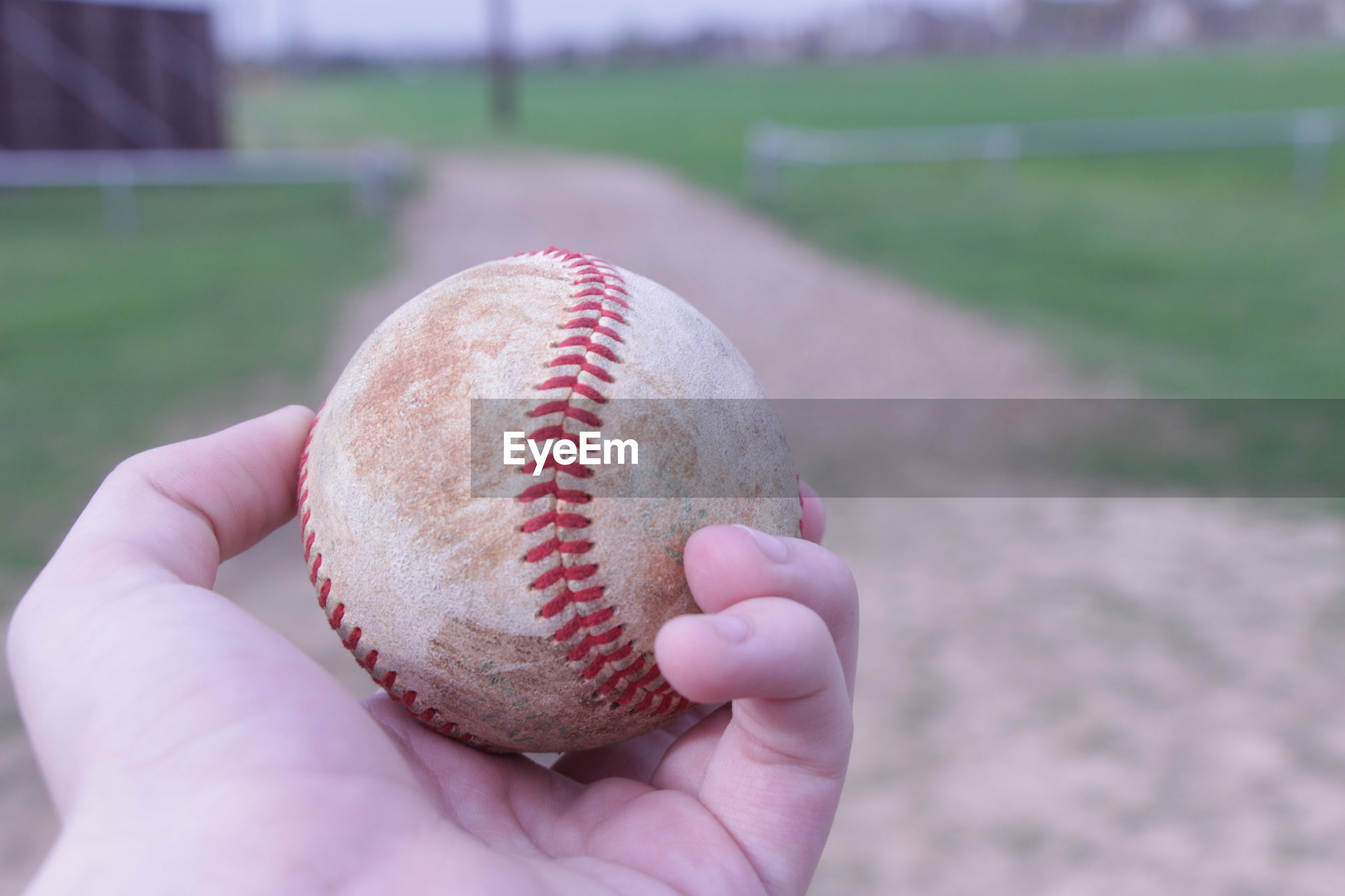 Cropped hand holding baseball on playing field