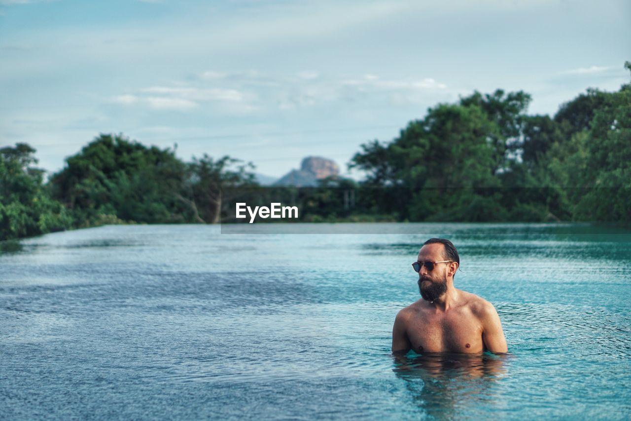 Shirtless man swimming in lake against sky